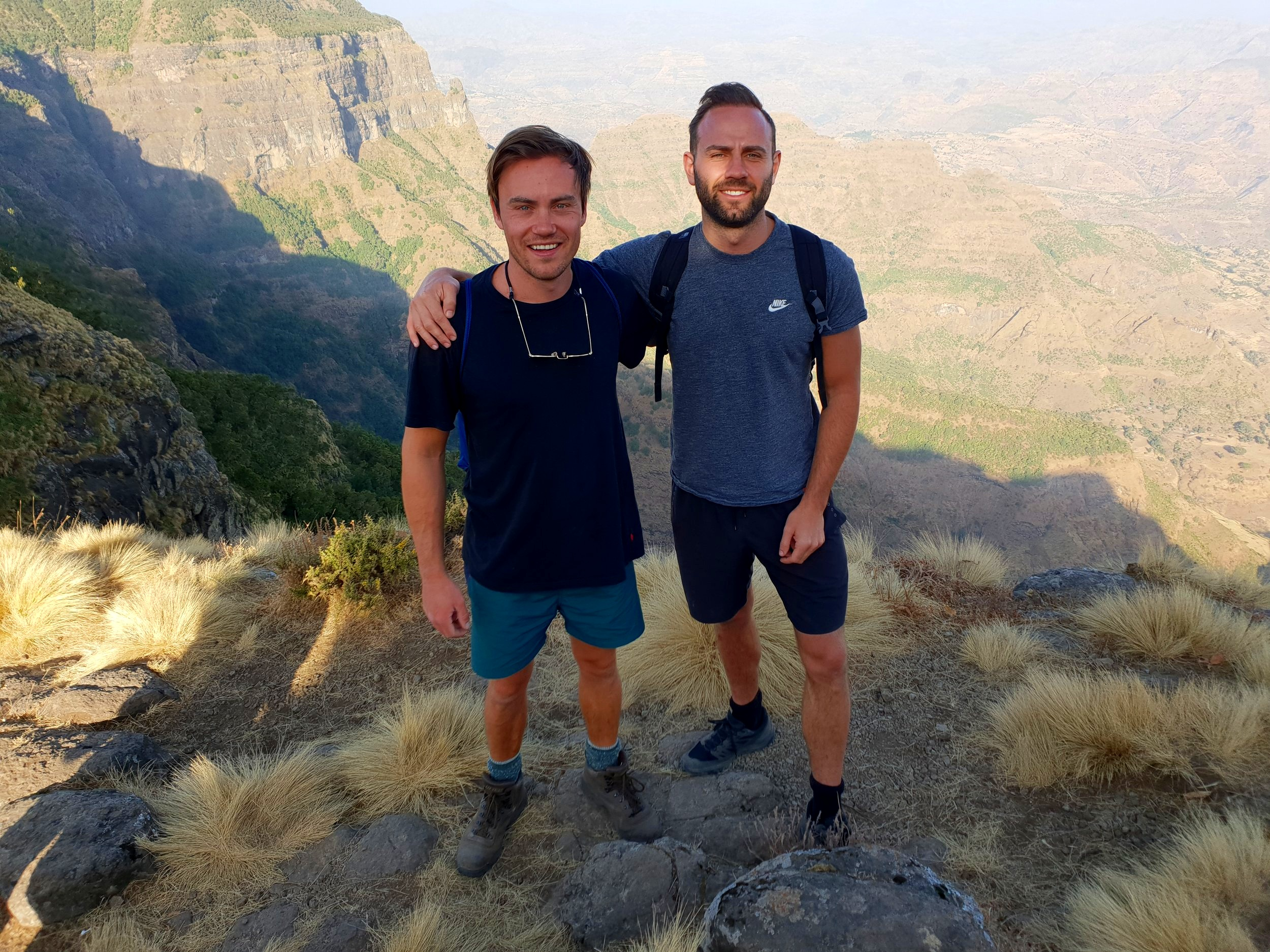 Two human friends stand near large cliff together, in the Simien Mountains.