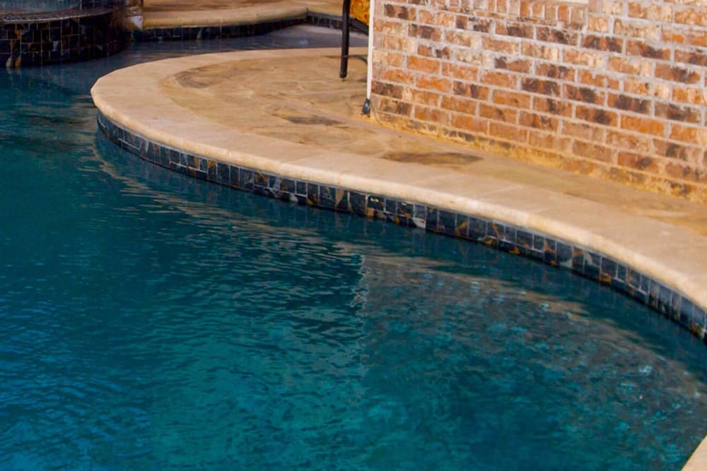 coping & tile - The coping is the capstone for the beam or wall of the pool. The coping can be made of many different materials ranging from concrete, brick, stone or pavers. Coping is a very important part of the pool visually as well as structurally. Coping allows the deck to shift and move freely without causing damage to the coping or pool wall. This is achieved by the expansion joint that separates the coping and the pool deck. Spartan Pool and Patio can remove your old coping and replace it with something that looks great again! You don't have to replace your old coping with the same material either. If we take out brick we can replace it with stone for example. You can browse all of our coping & tile options here.