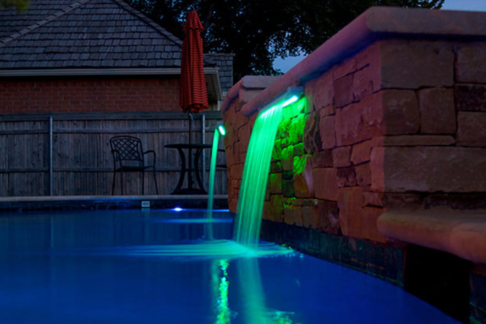 water features - We have the ability to create a wide variety of water features to compliment and enhance your swimming pool. The peaceful sound of running water can take your backyard to the next level. Wether you just want something small to add the final touch to your project or something large that will really stand out and provide a focal point for entertaining guests, we are confident that we can provide what you need. Water features can also be used to mask environmental noises such as traffic or loud neighbors. We also can offer lighting within the water features that will really make a statement at night.