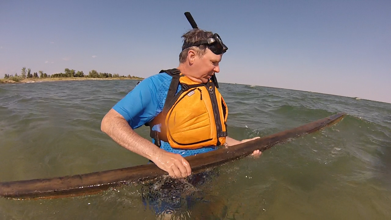 Wes examines a board found on the bottom of Tawas Bay, MI.