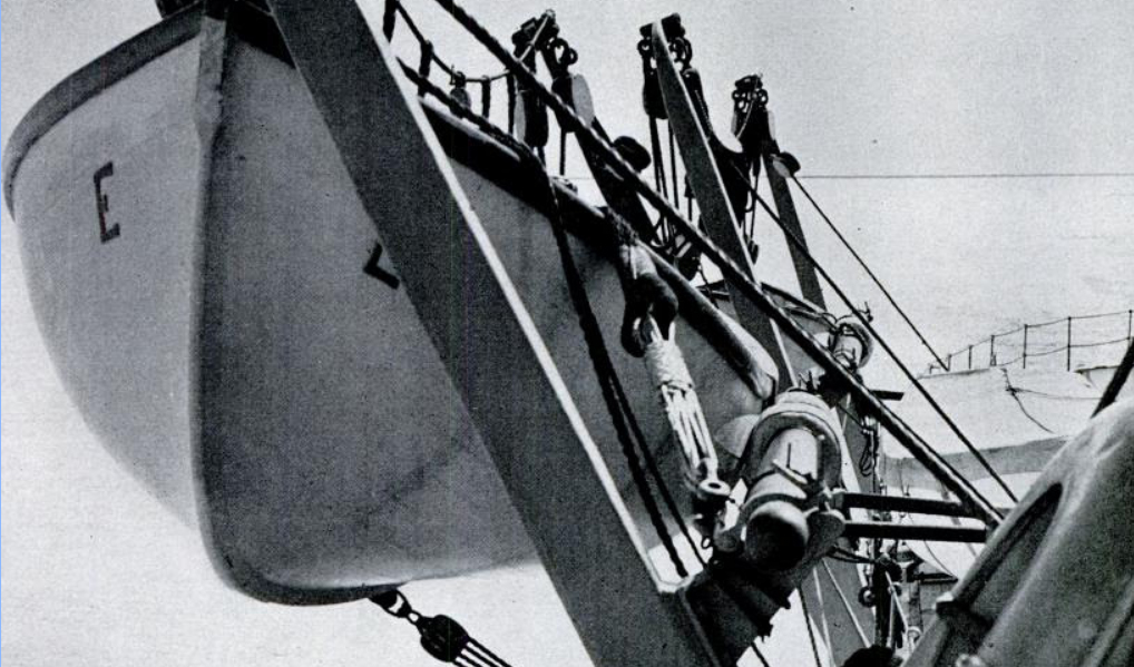 A close-up of the lifeboat and strong-back (lower right pole).