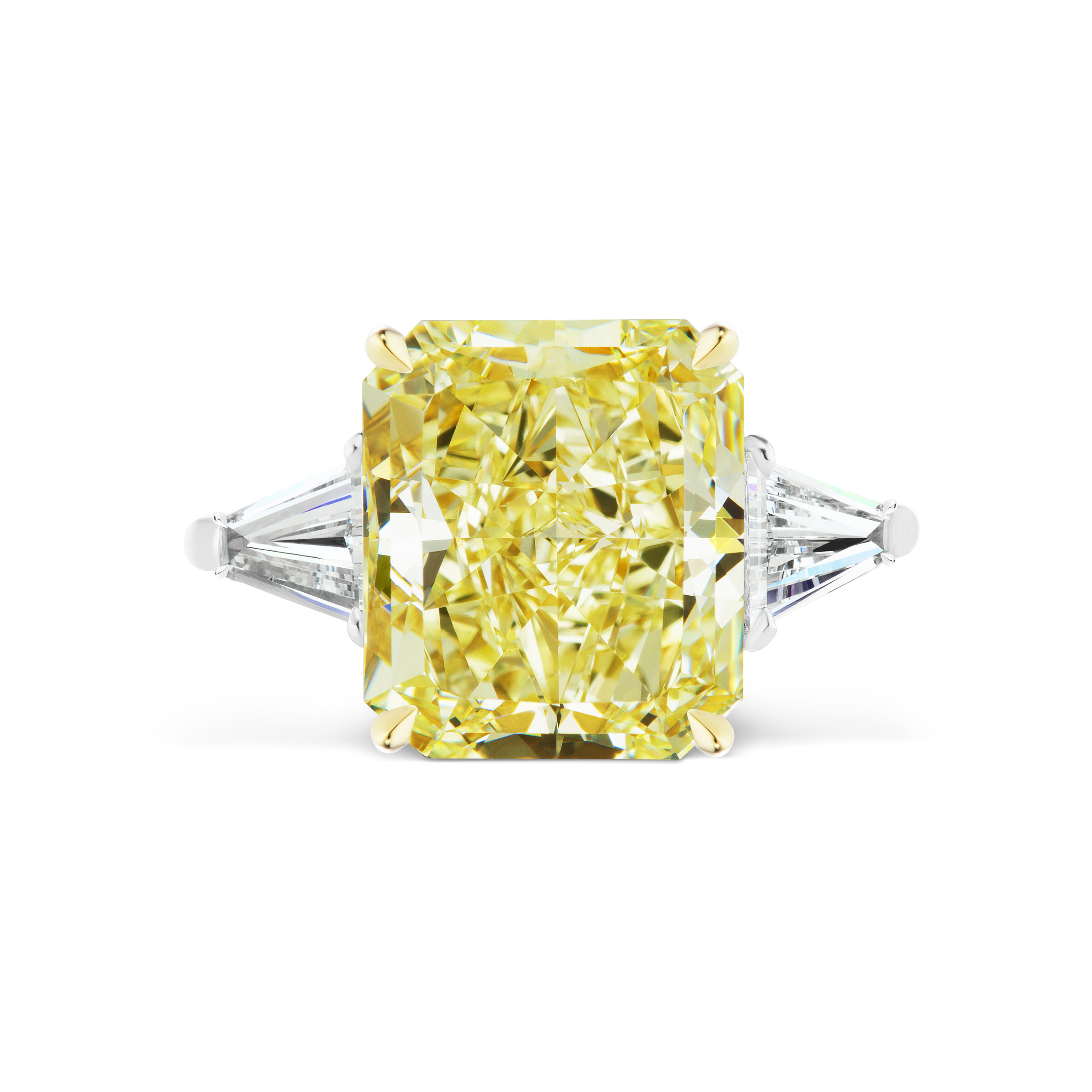Radiant cut yellow diamond ring with tapered baguette side stones, mounted in platinum.