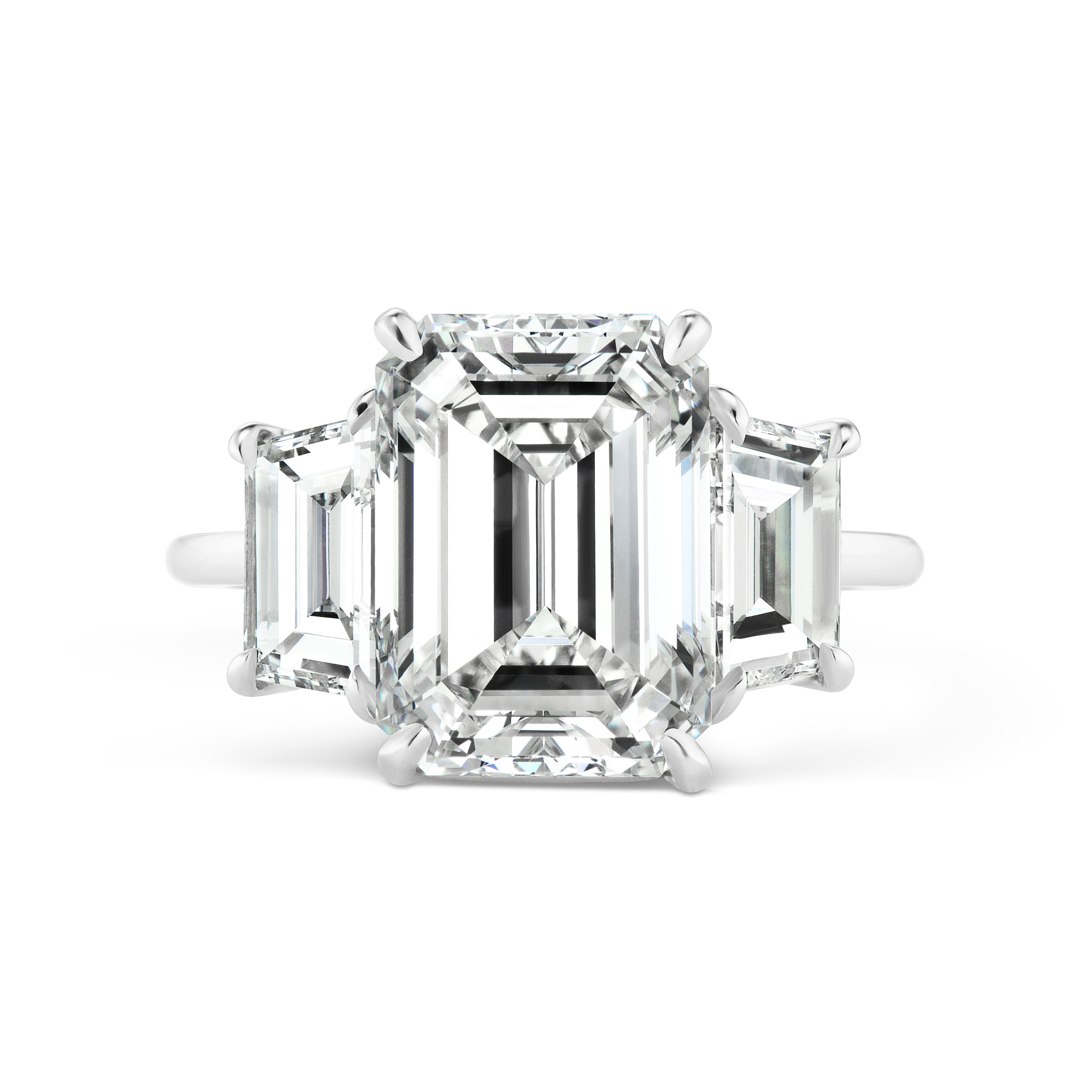 Emerald cut diamond ring with trapezoid side stones, mounted in platinum.
