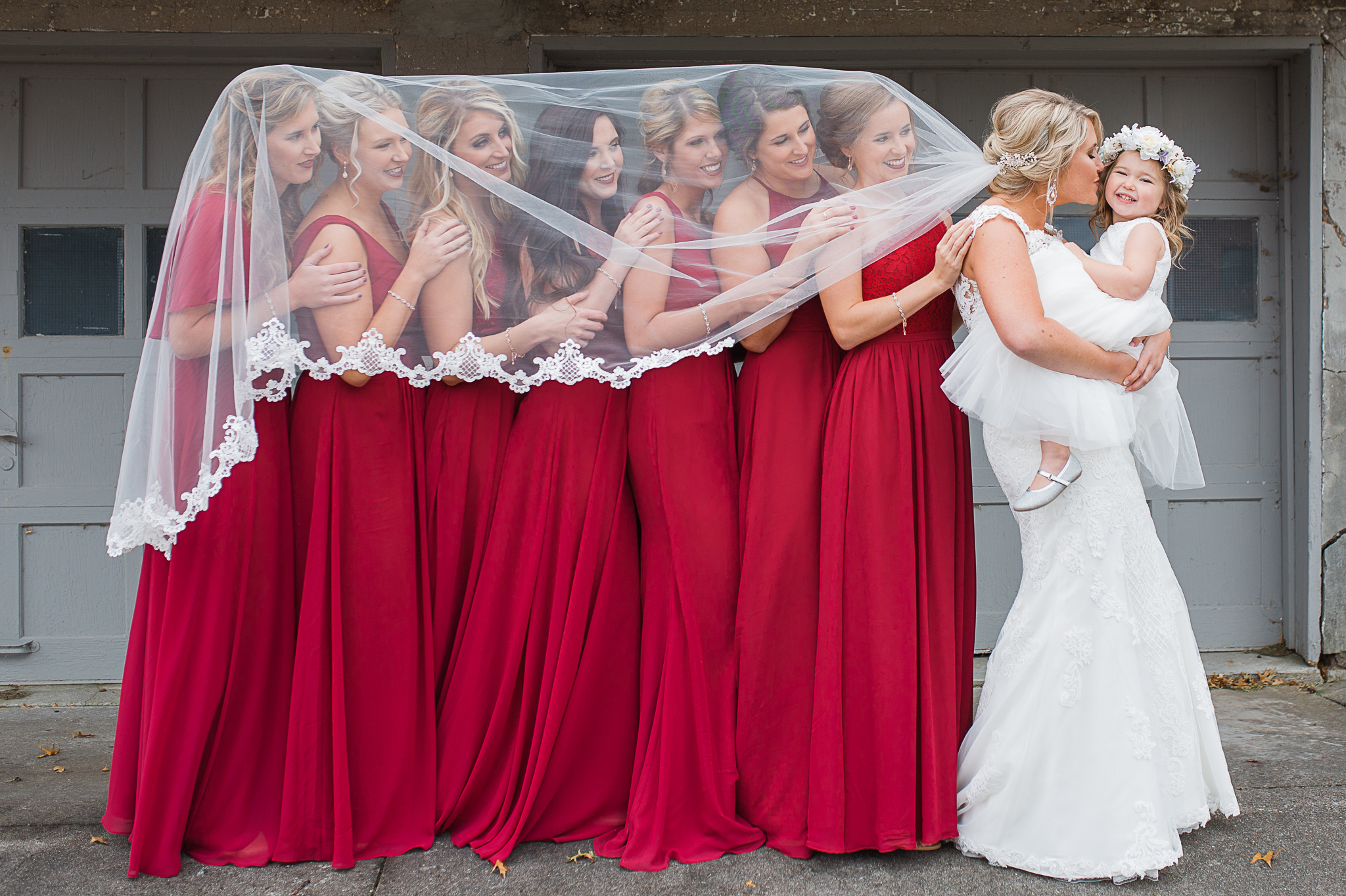 Bridal party under brides veil with flower girl