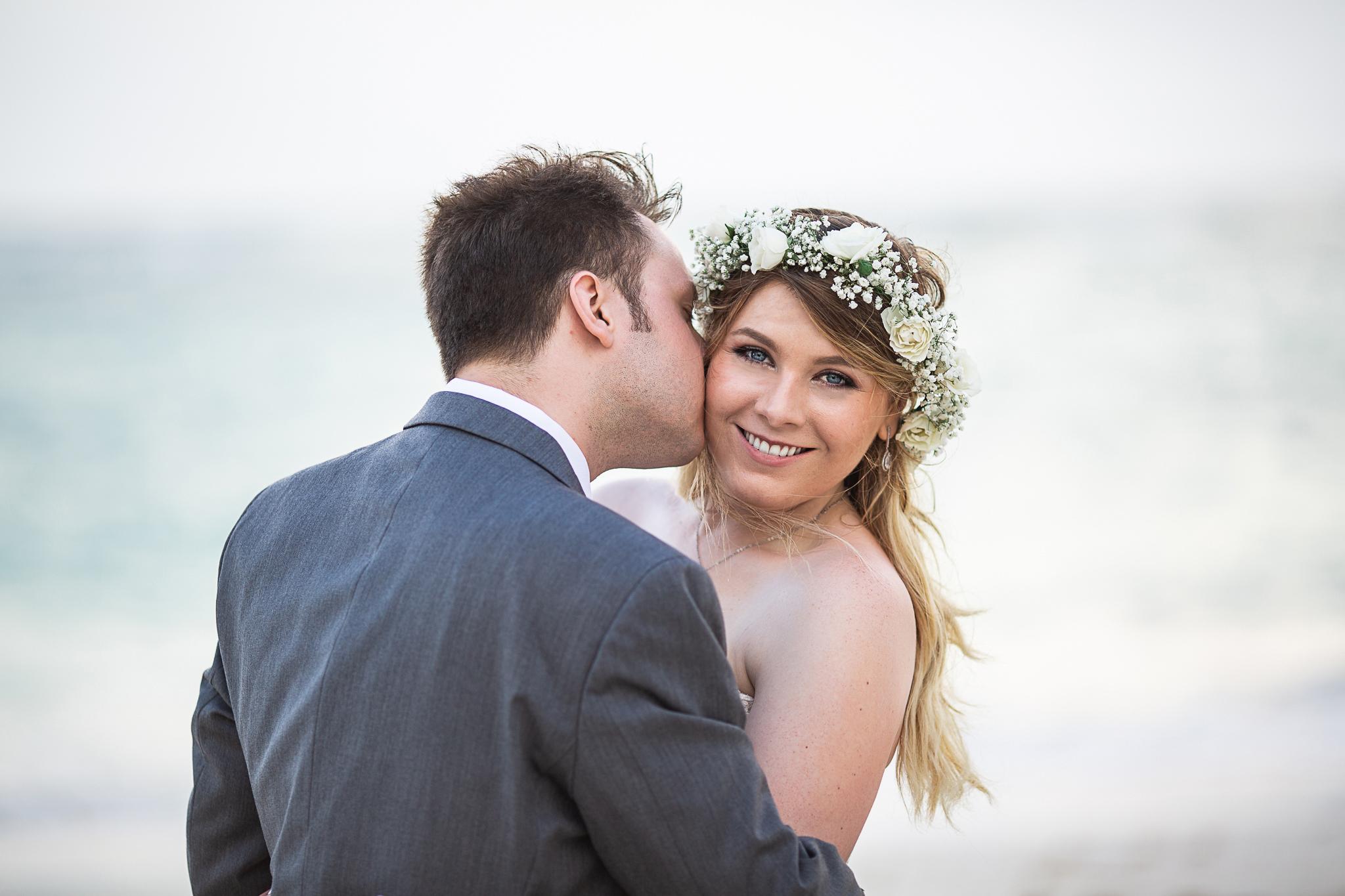 Bride and groom kissing on cheek