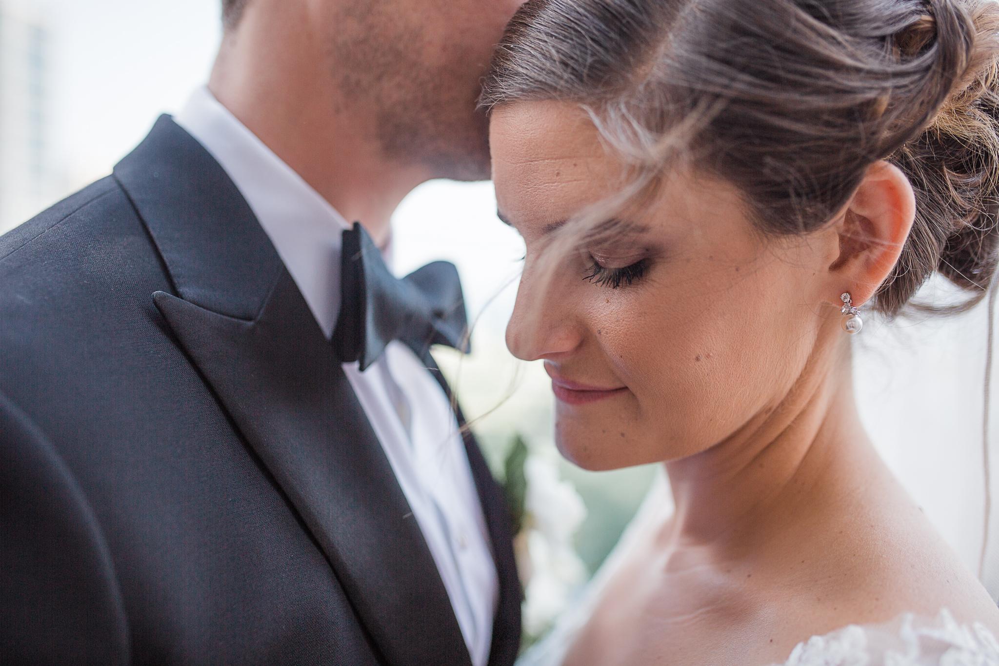 Groom kissing bride on temple