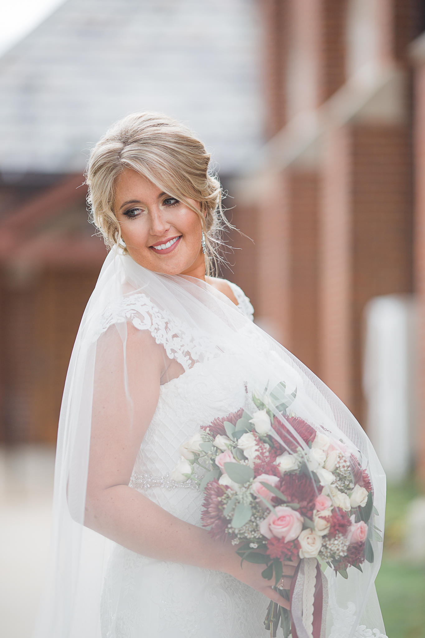 Bride posing with flowers and veil