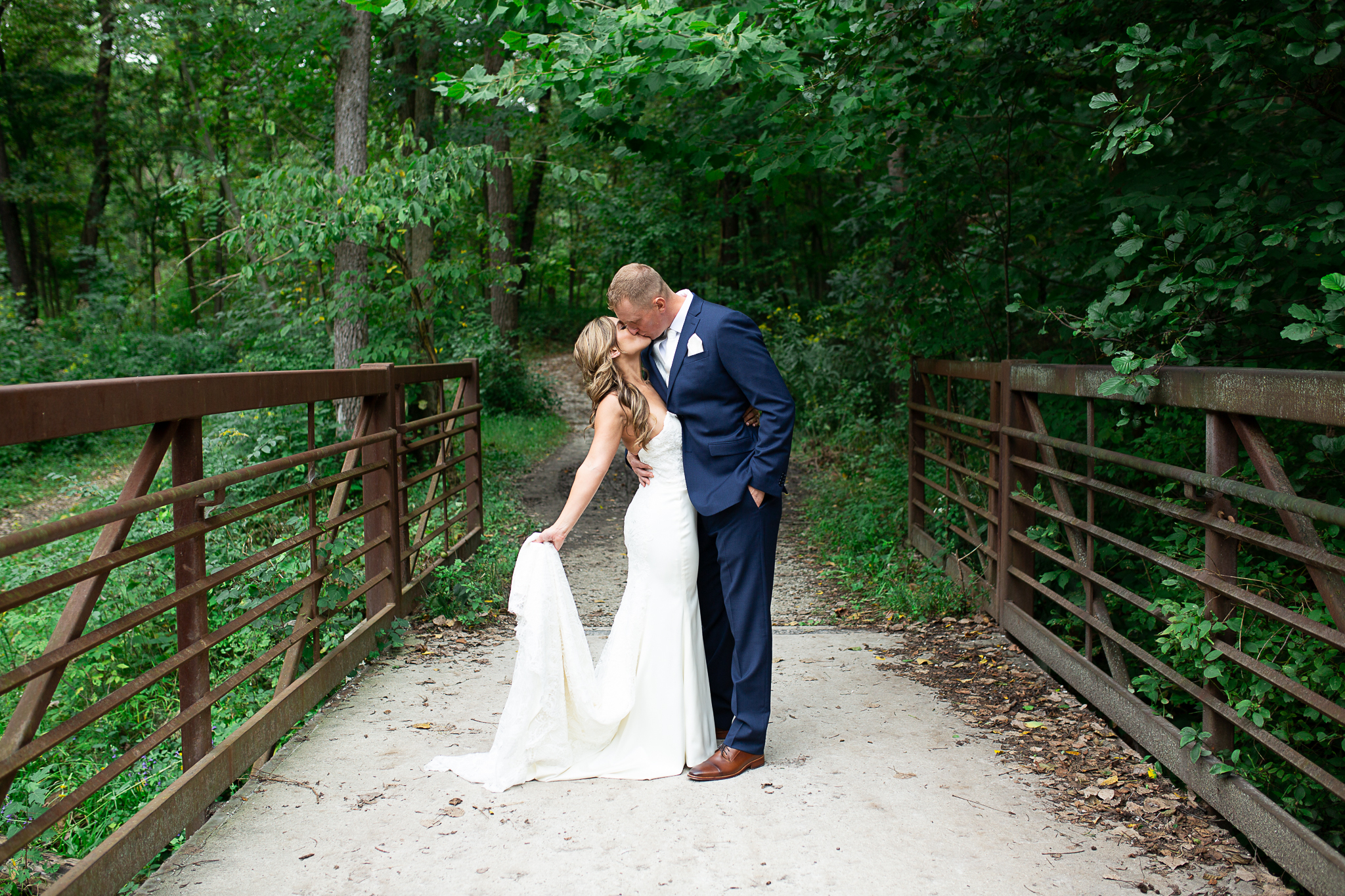 Bride and groom posing on a bridge in the woods