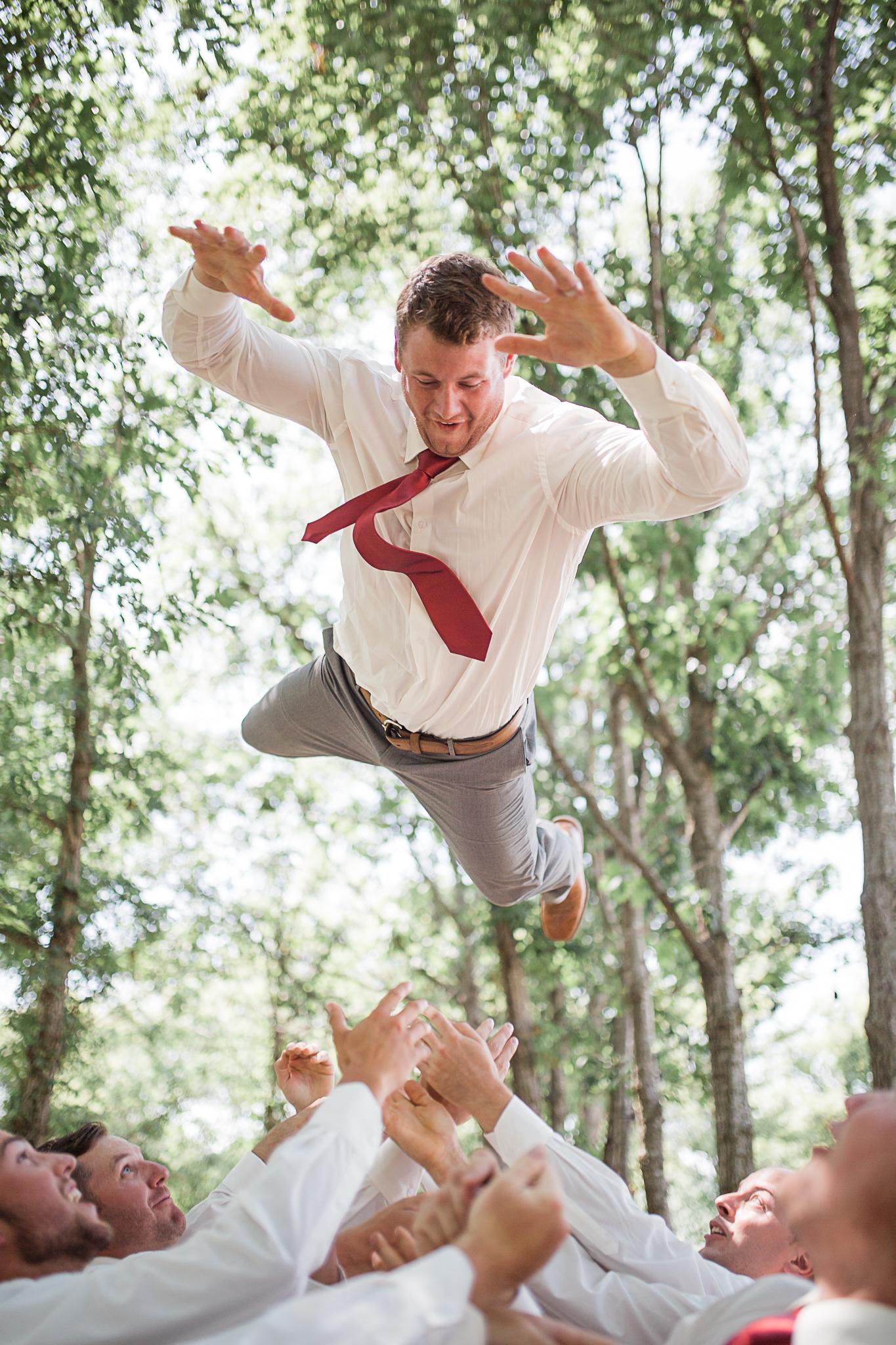 Groom toss by groomsmen outdoors