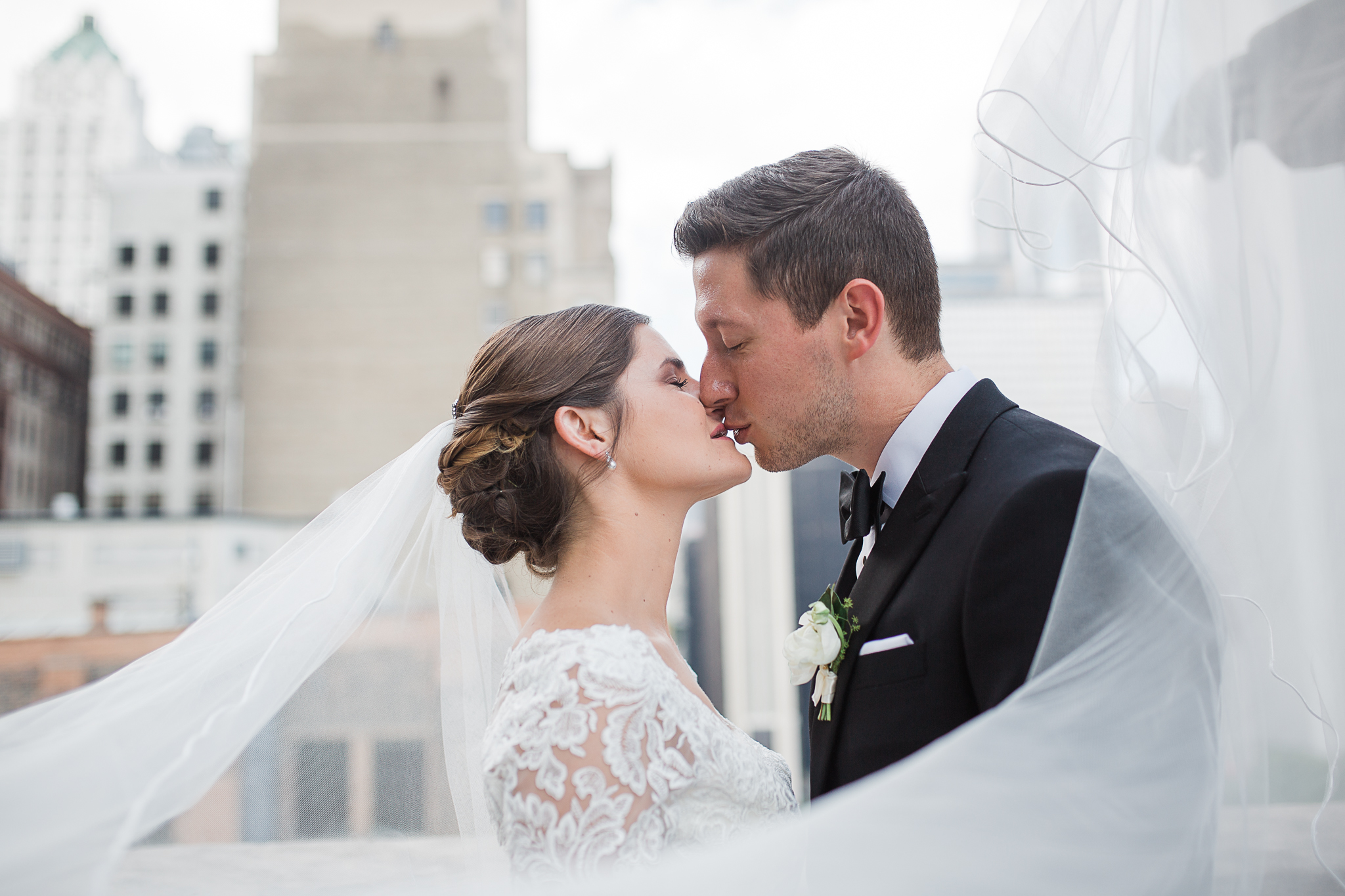 bride and groom kissing on downtown Chicago rooftop