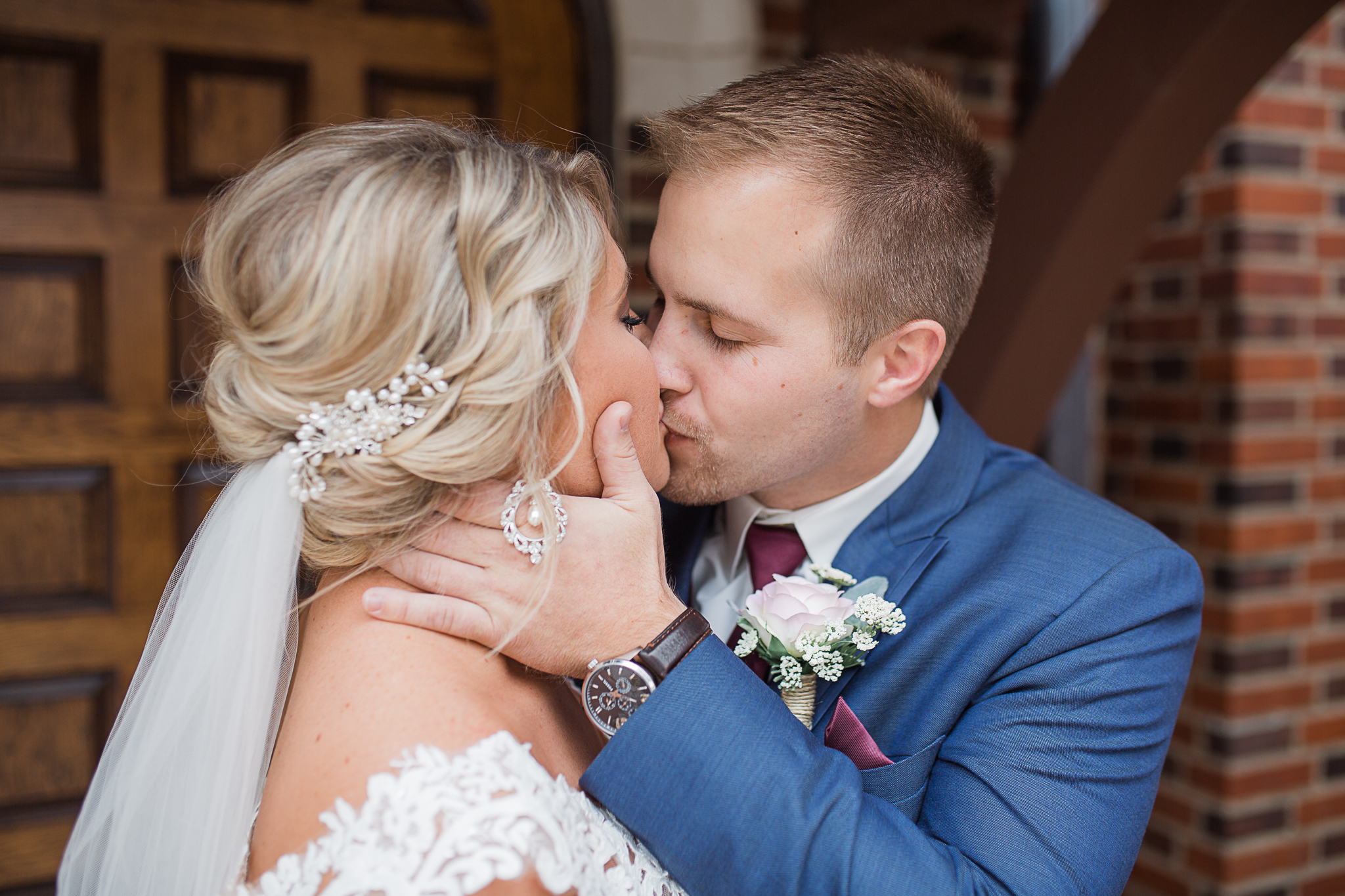 bride and groom kissing outside of church