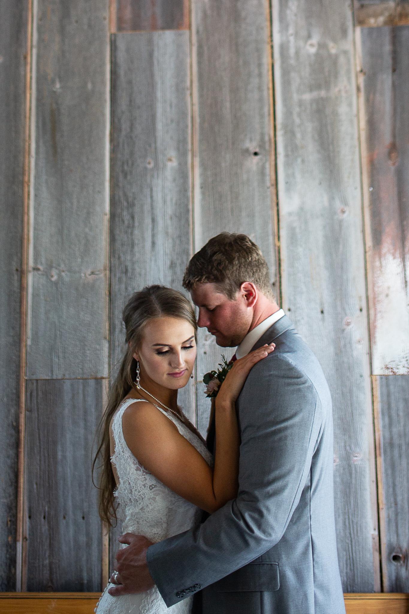 bride and groom poses inside barn