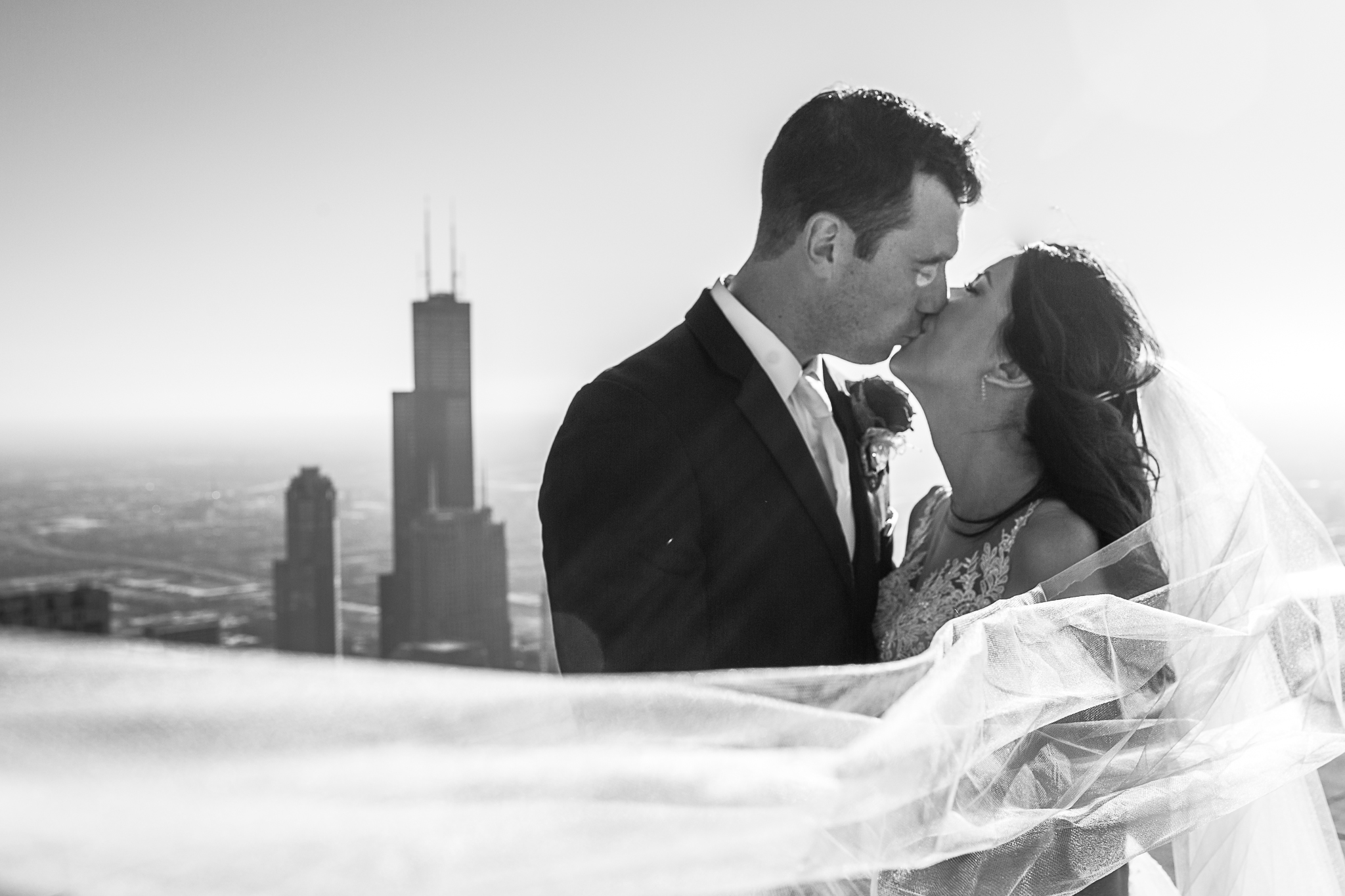 Bride and groom kissing on top of rooftop in Chicago