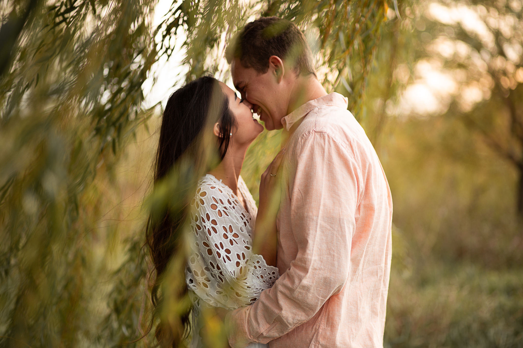 Couple outdoors kissing by trees