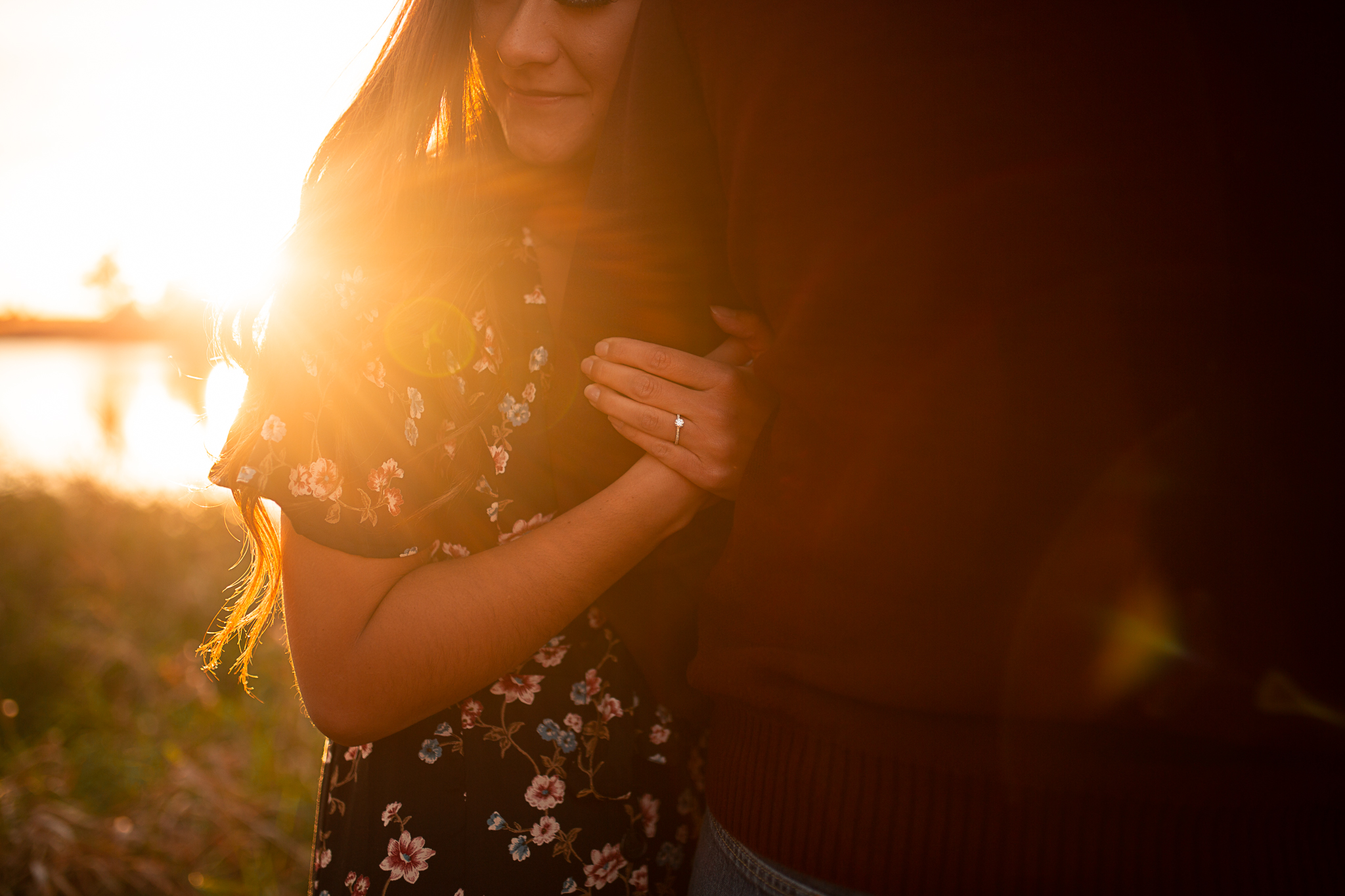 Fiance holding boyfriends arm at sunset