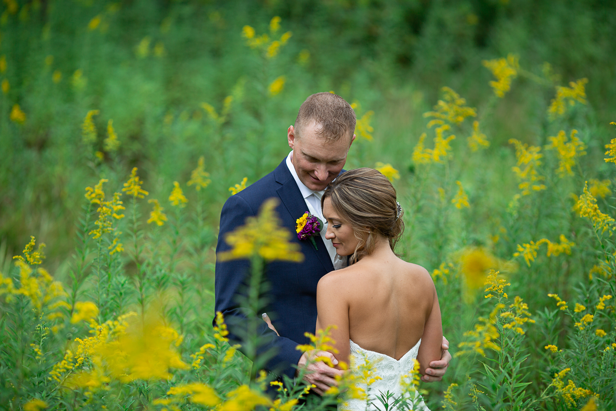 bride and groom in field with yellow flowers