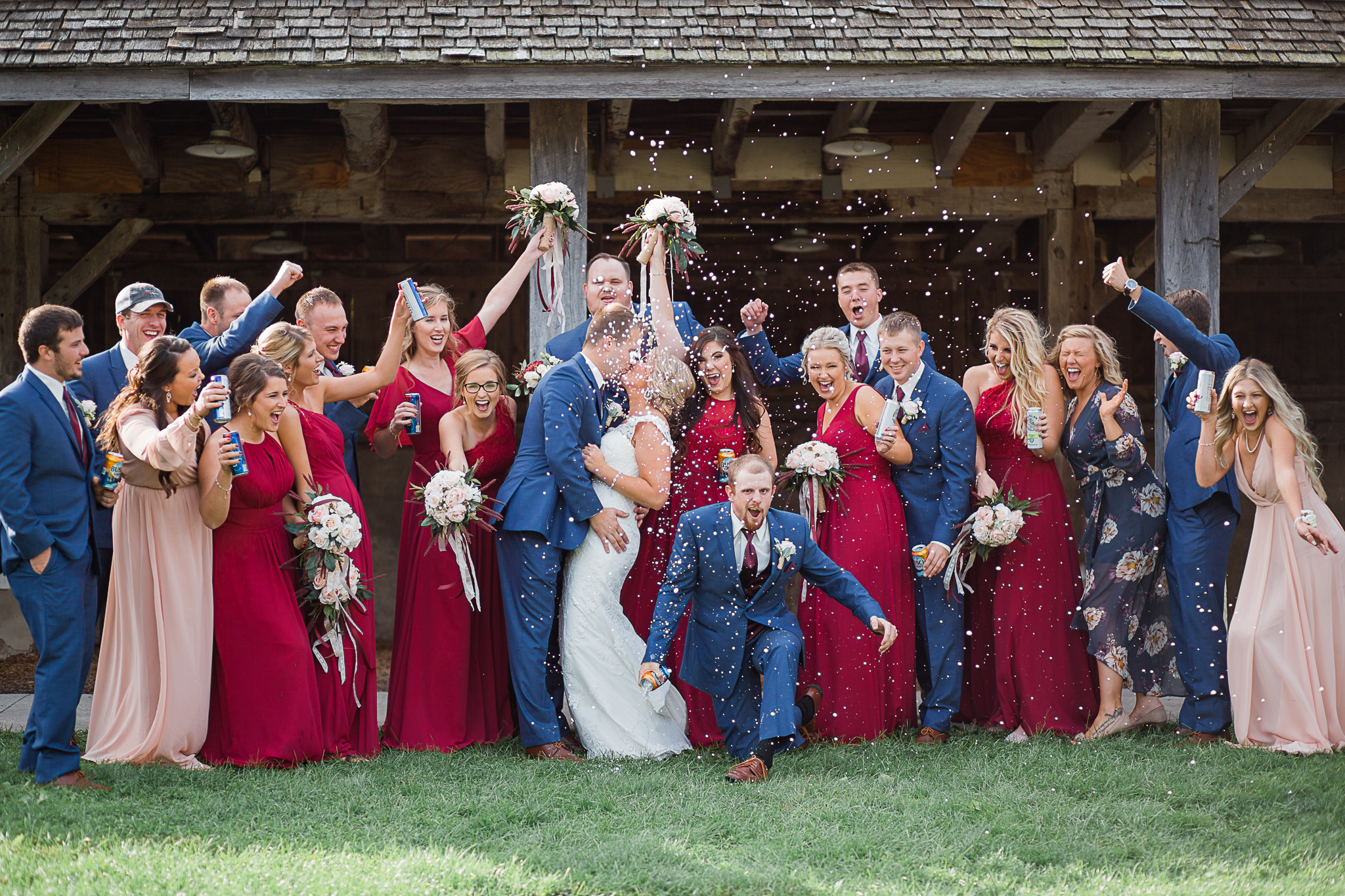 bride and groom kissing with bridal party cheering