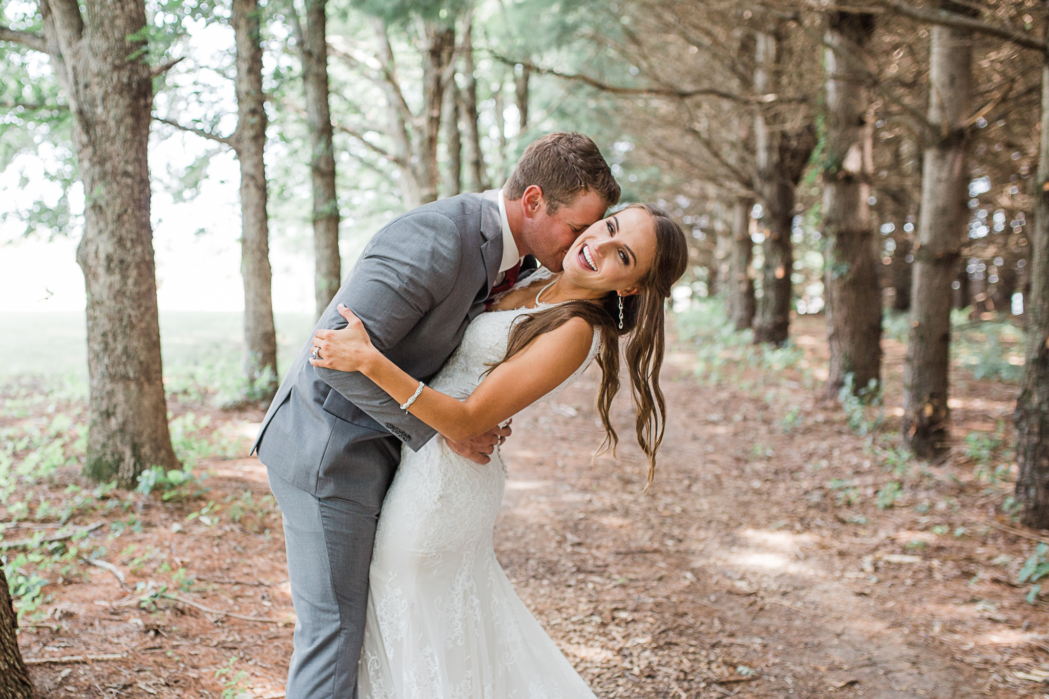Groom leaning in and kissing bride in the forest