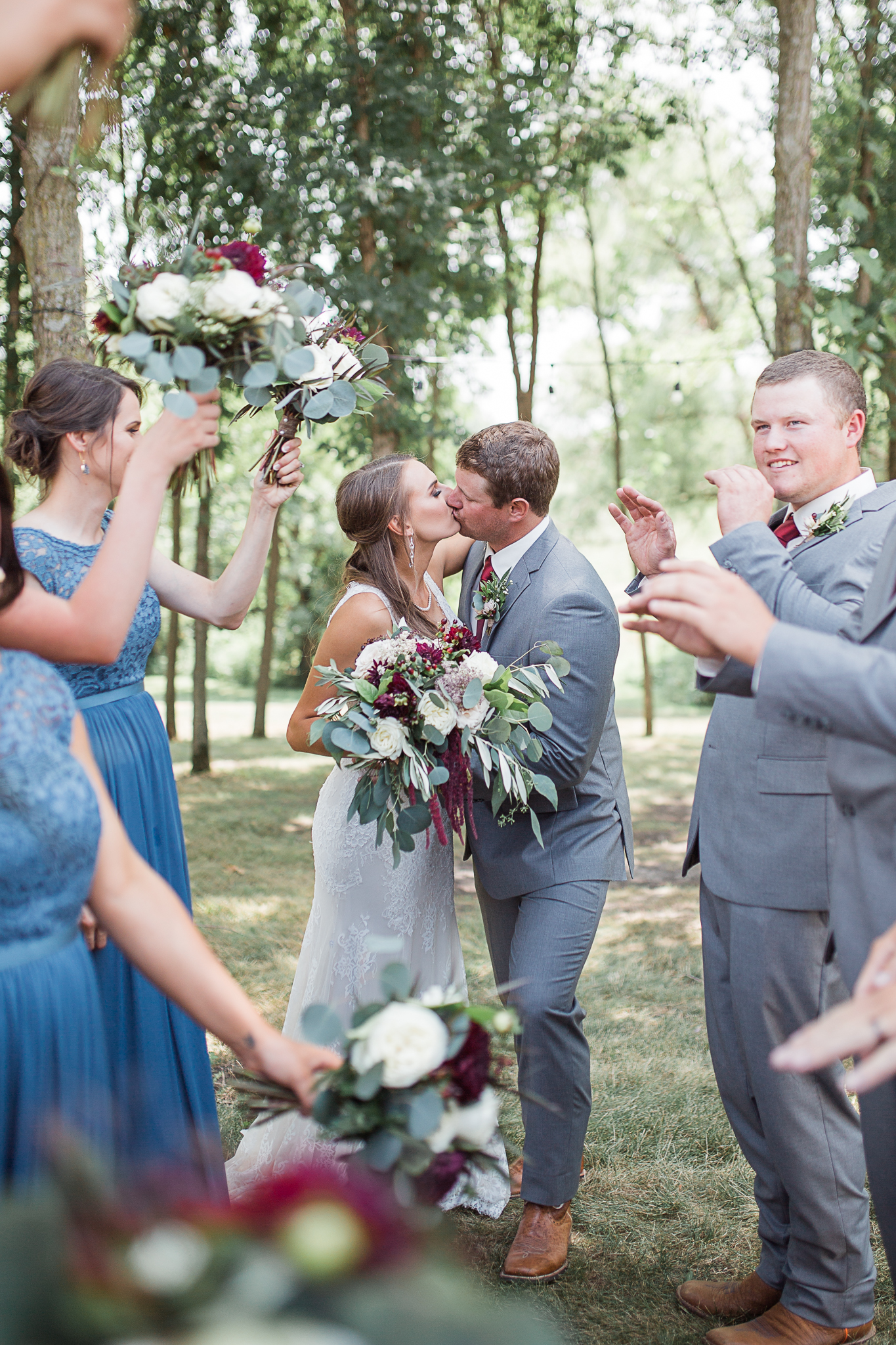 Bride and groom kissing with bridal party cheering and celebrating