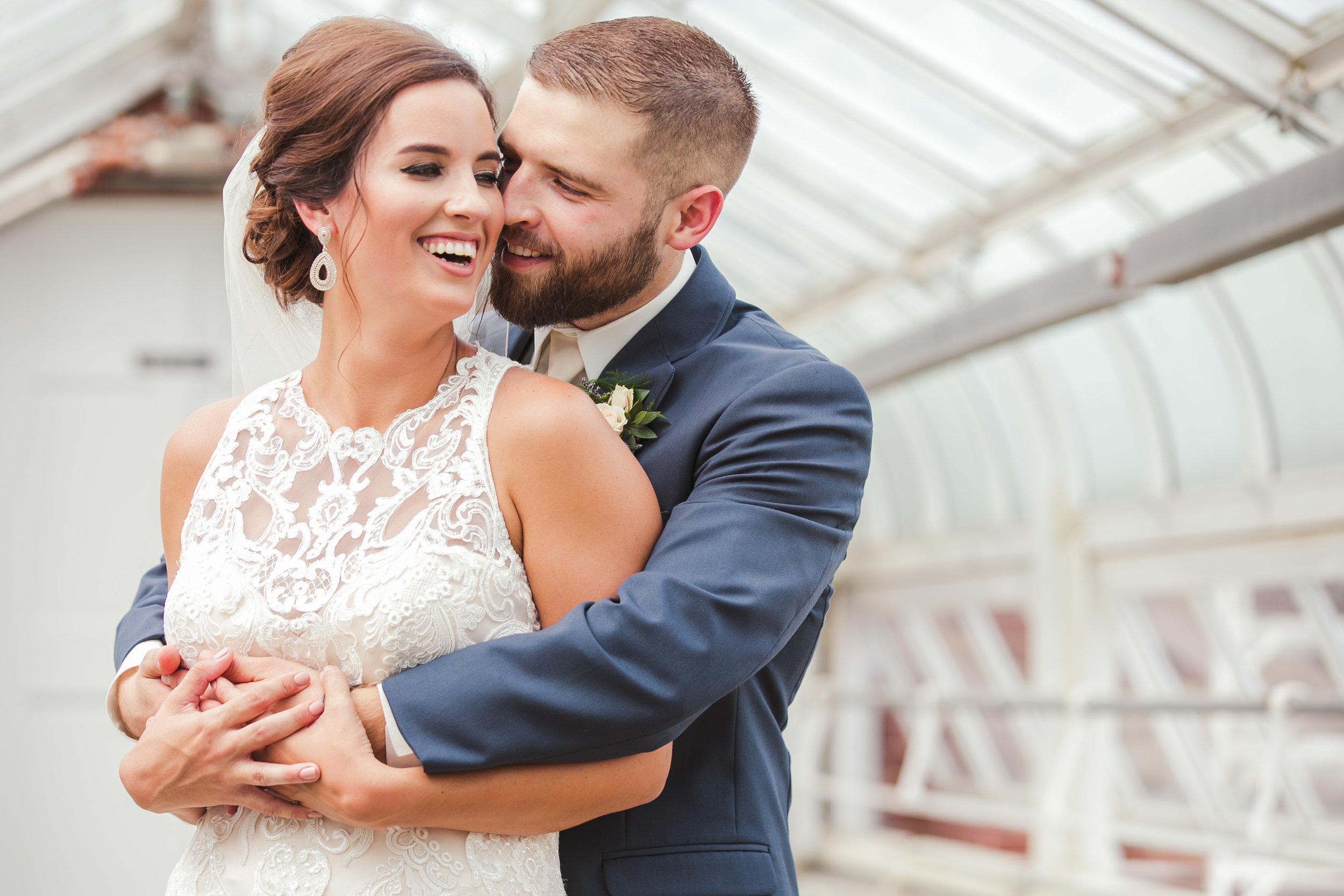 Groom hugging bride in greenhouse