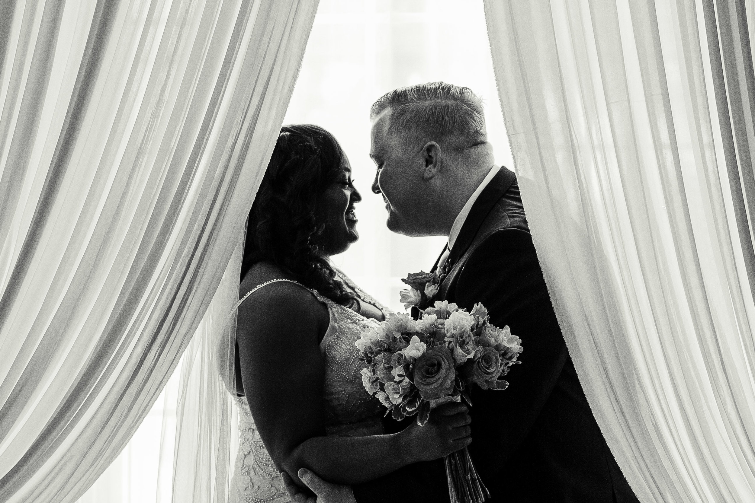 bride and groom hugging behind curtains