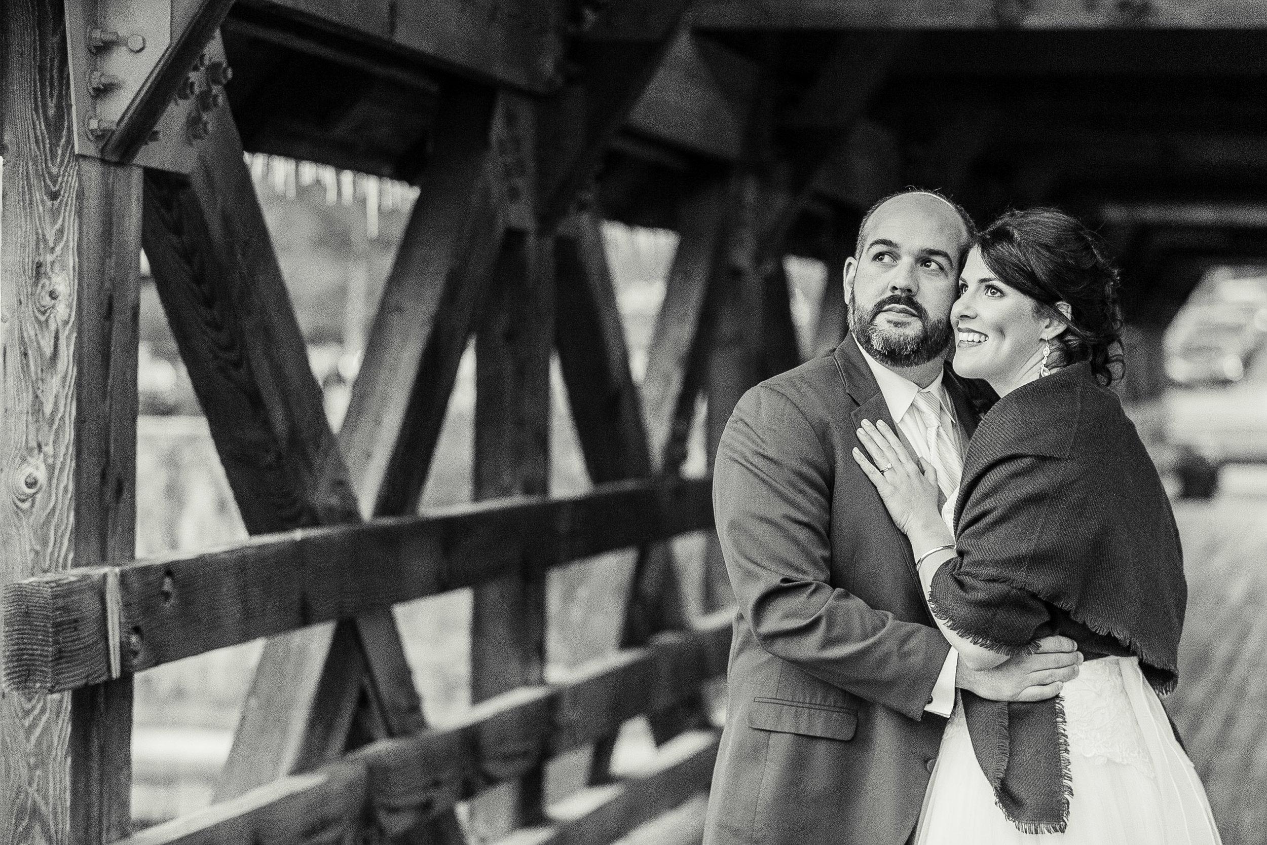bride and groom posing on bridge