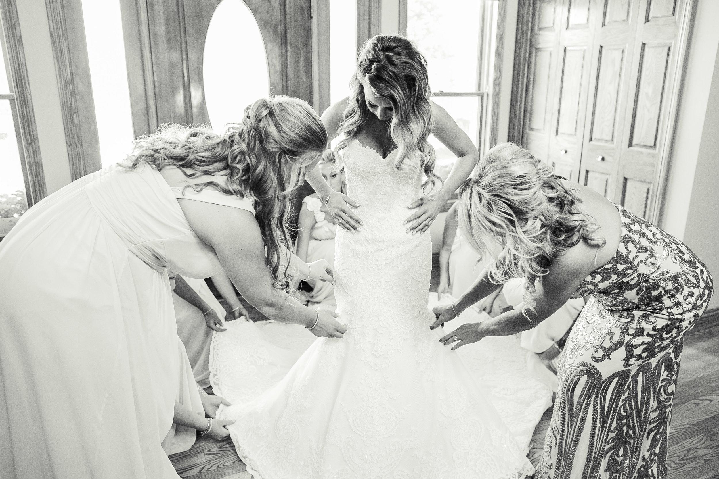 bridesmaids helping bride put dress on