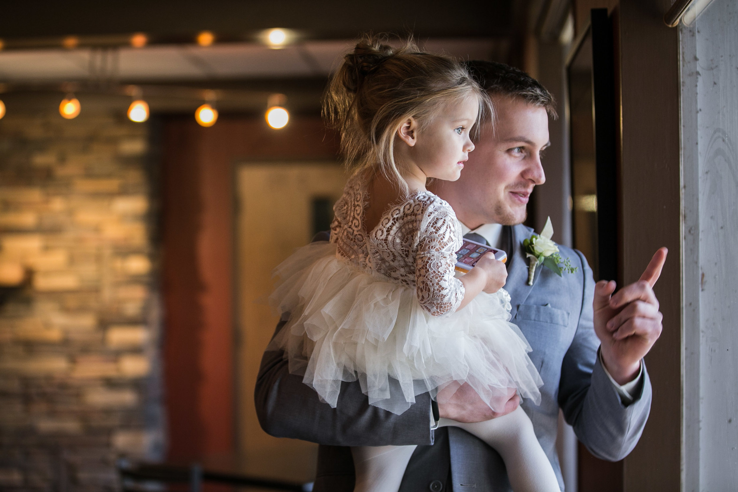 groom and daughter looking out the window before wedding ceremony