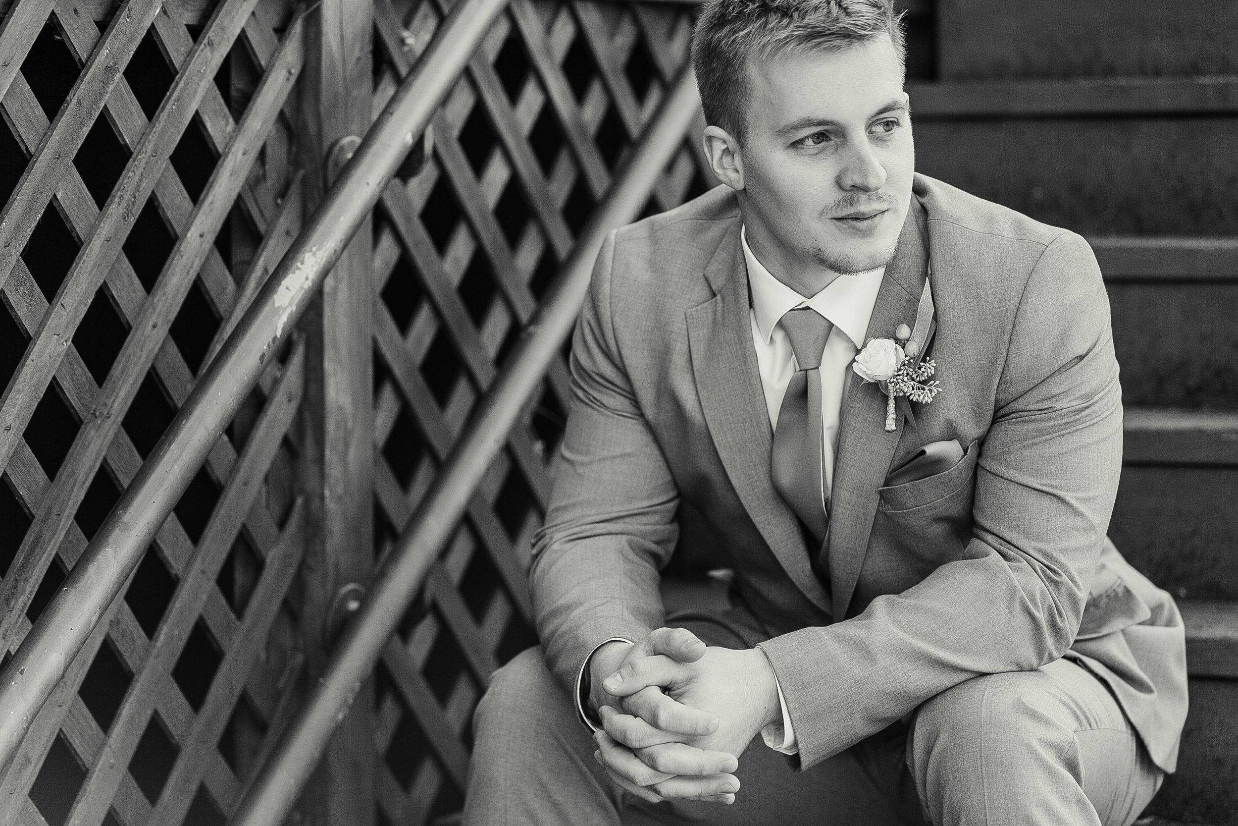 groom posing on stairs outdoors