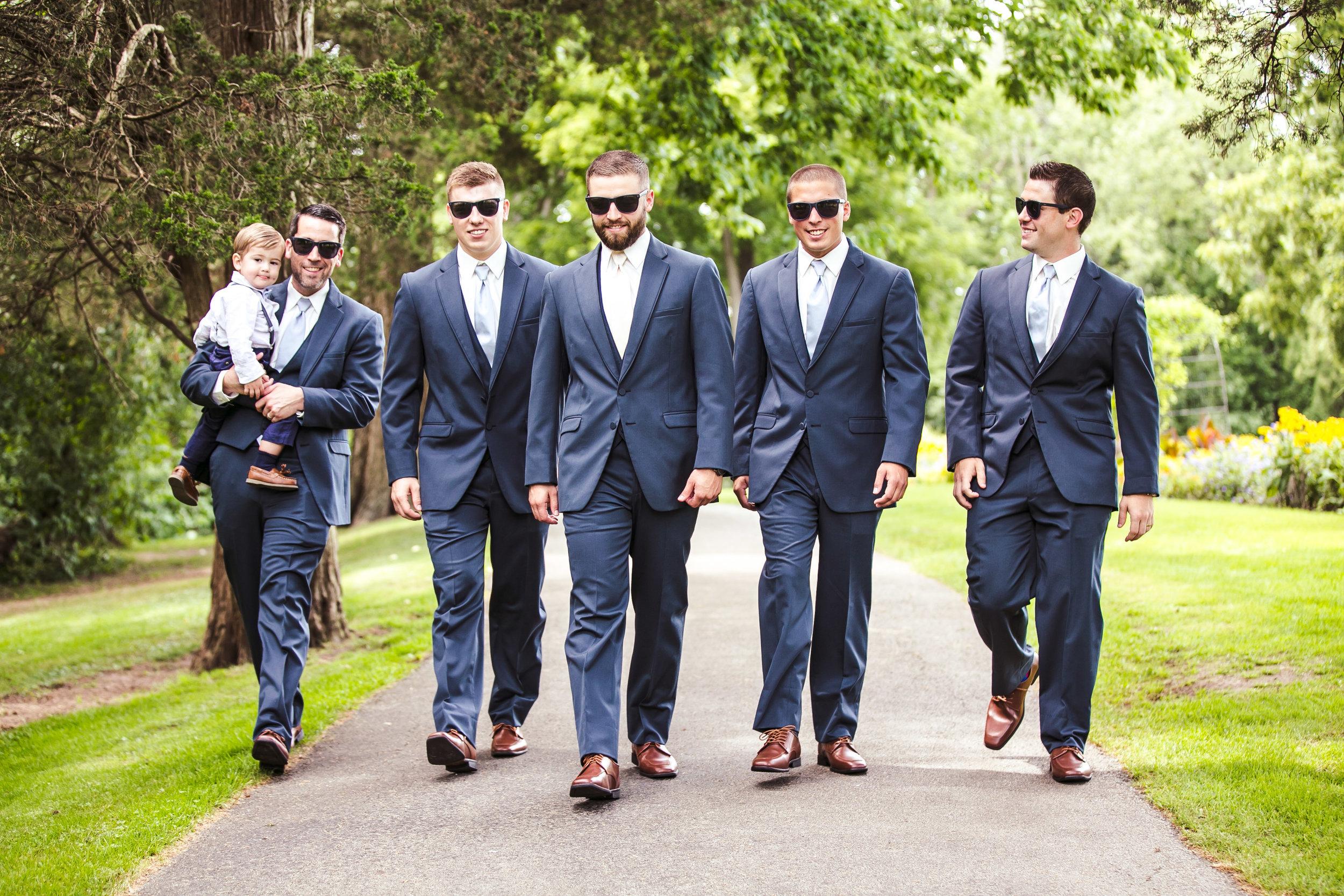 groom and groomsmen walking down wooded trail