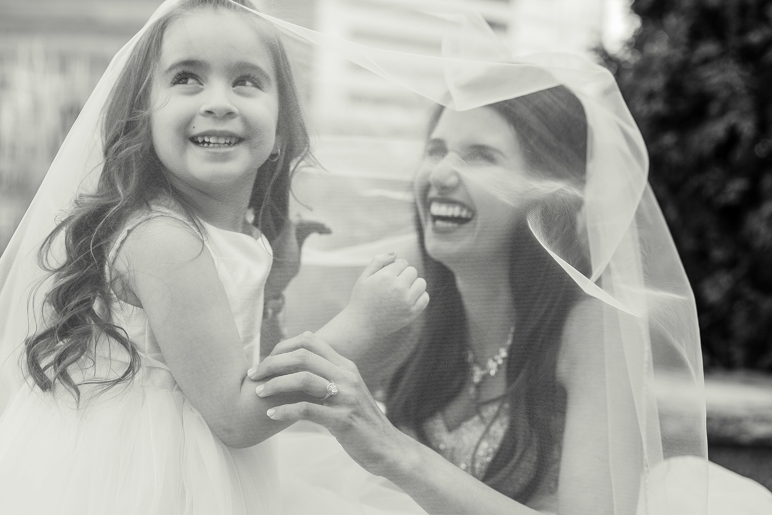 bride laughing with flower girl under her veil