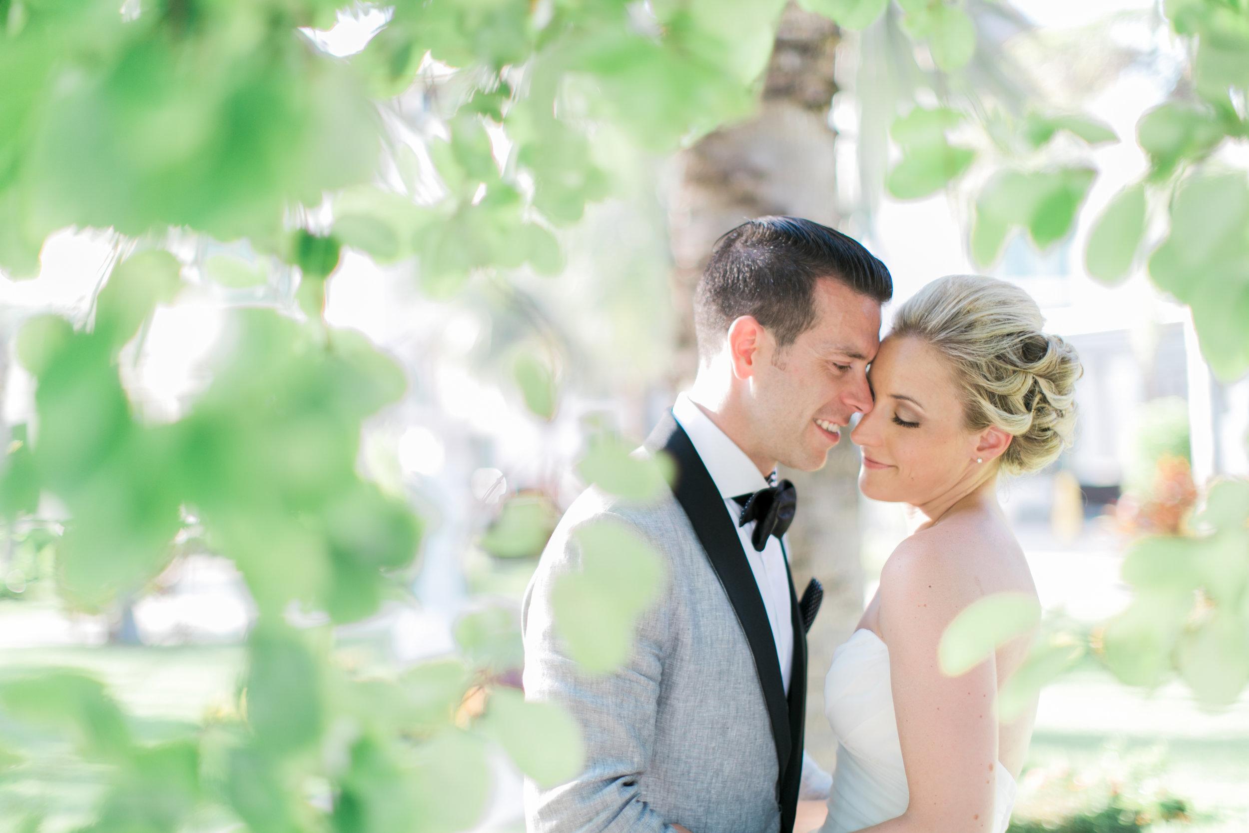 Bride and groom hugging under greenery.