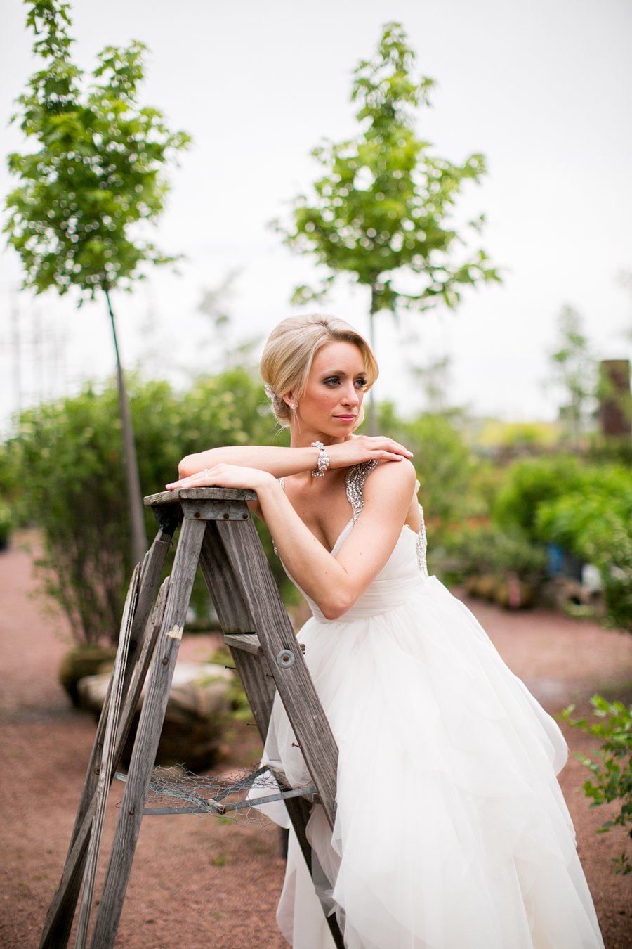 Bridal session with bride leaning on a ladder.