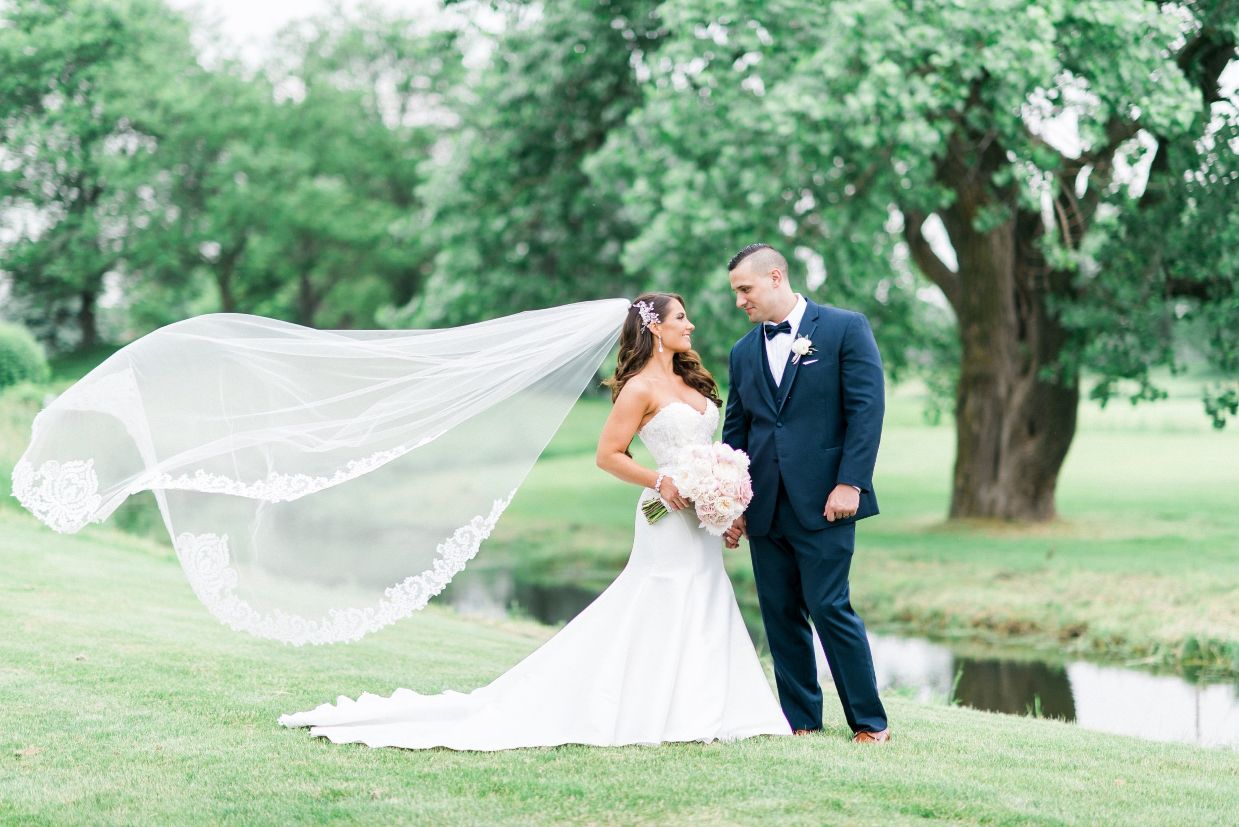 Bride and groom veil shot on golf course.