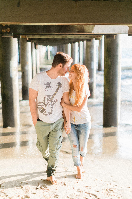 Engaged couple walking under board walk.