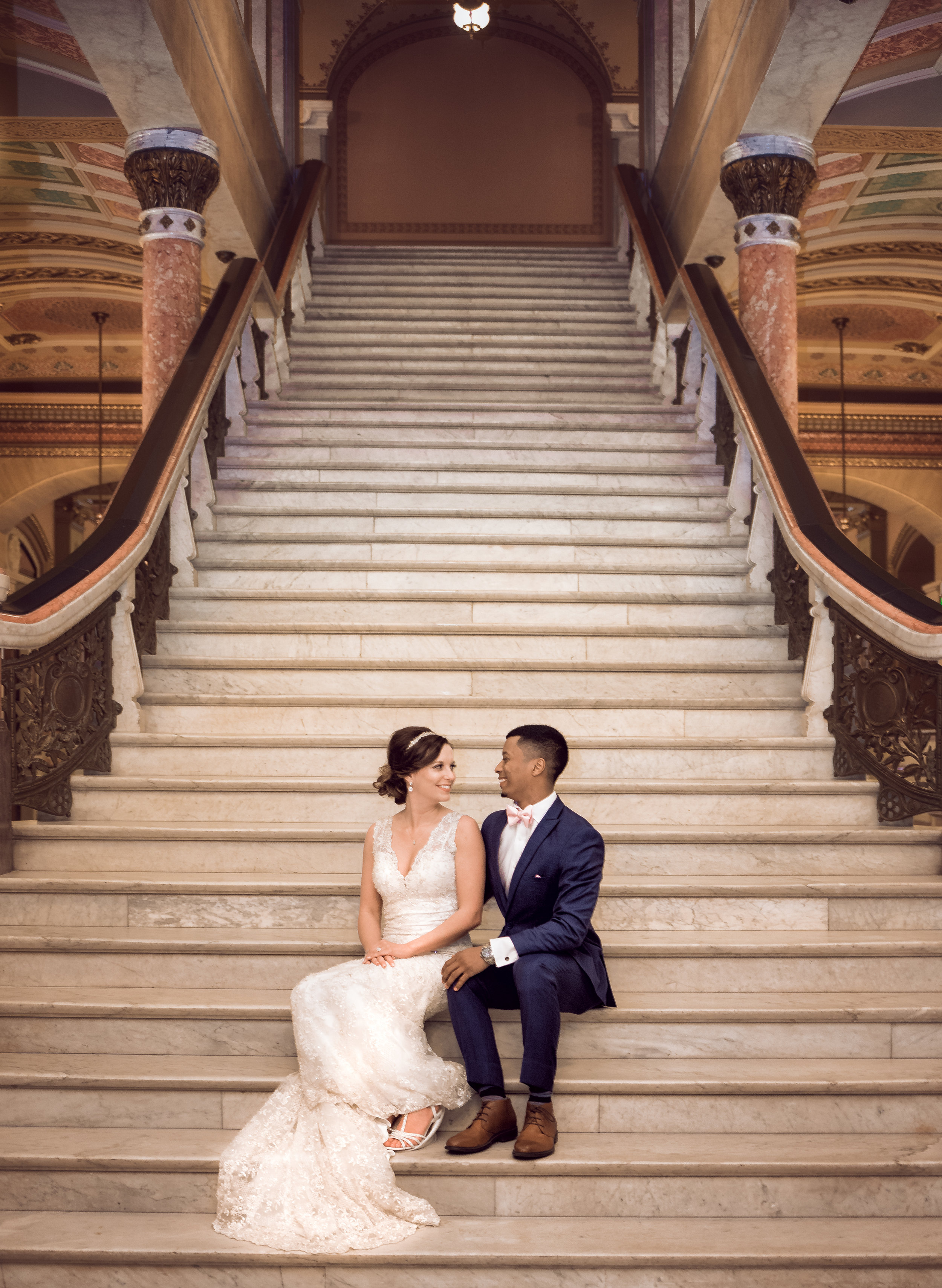 bride-groom-sitting-stairs-palace-loving-smiles.jpg