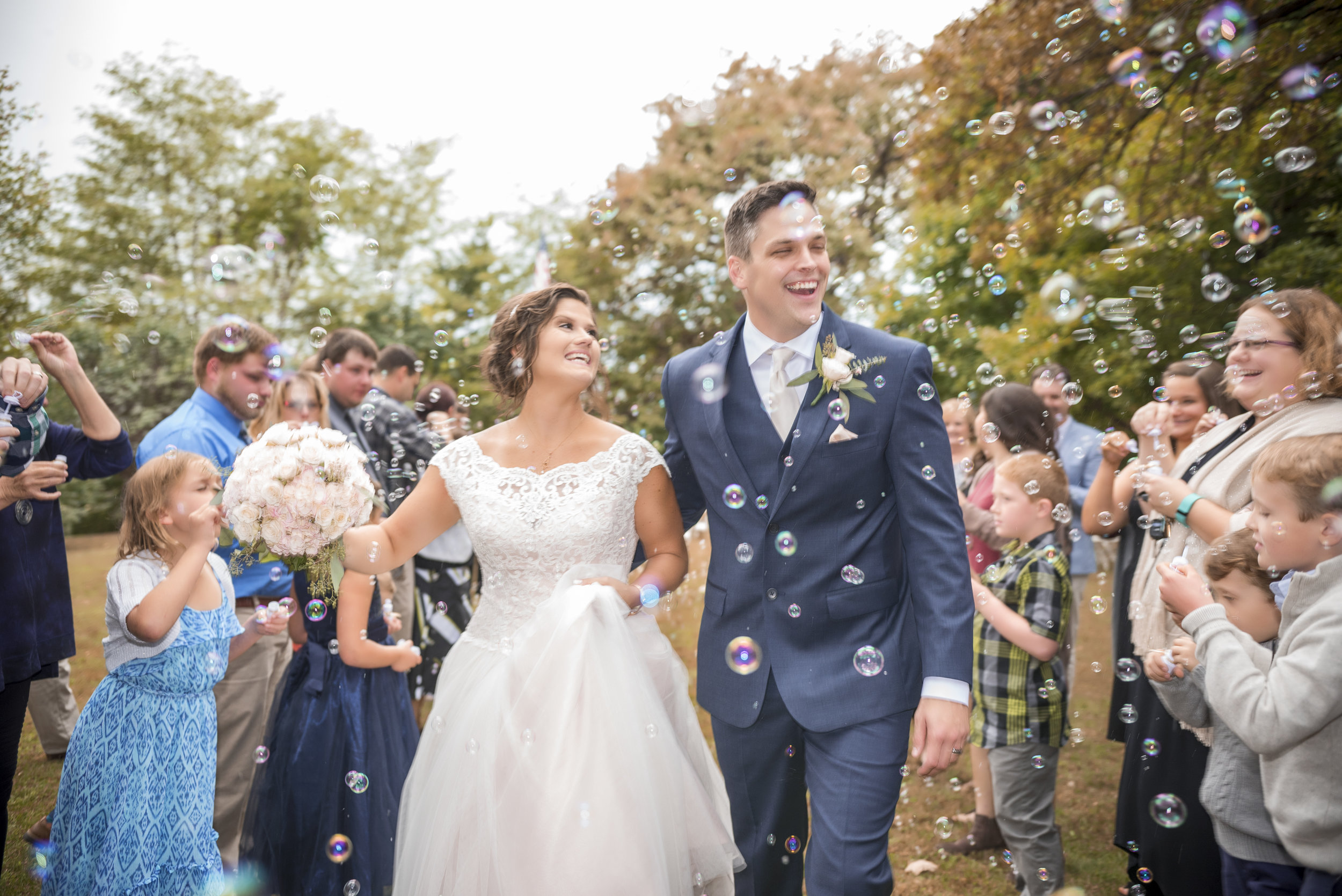 bride-groom-bouquet-bubbles-wedding-crowd-smiling.jpg