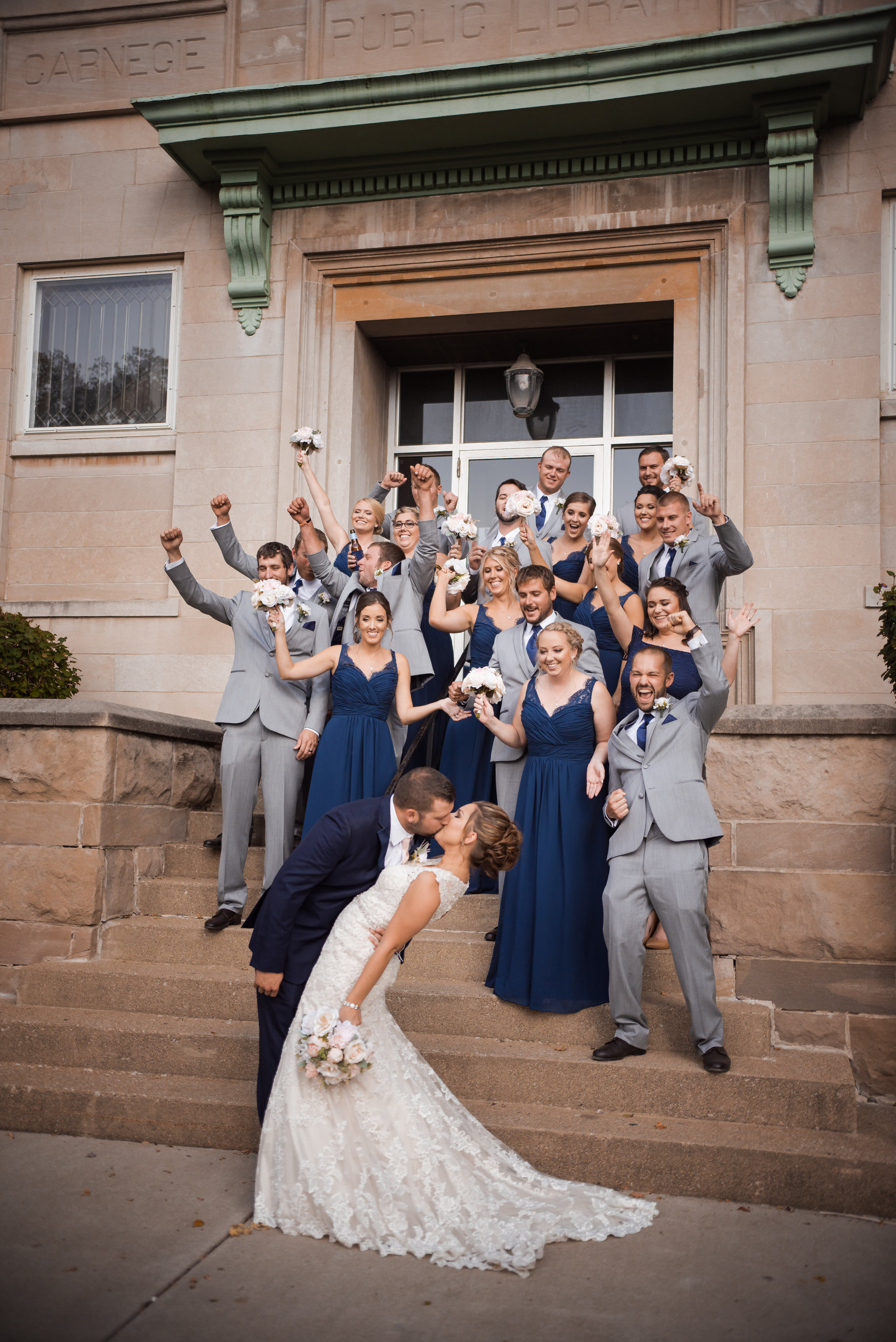 carnegie-library-bride-groom-kissing-bridesmaids-groomsmen-cheering.jpg