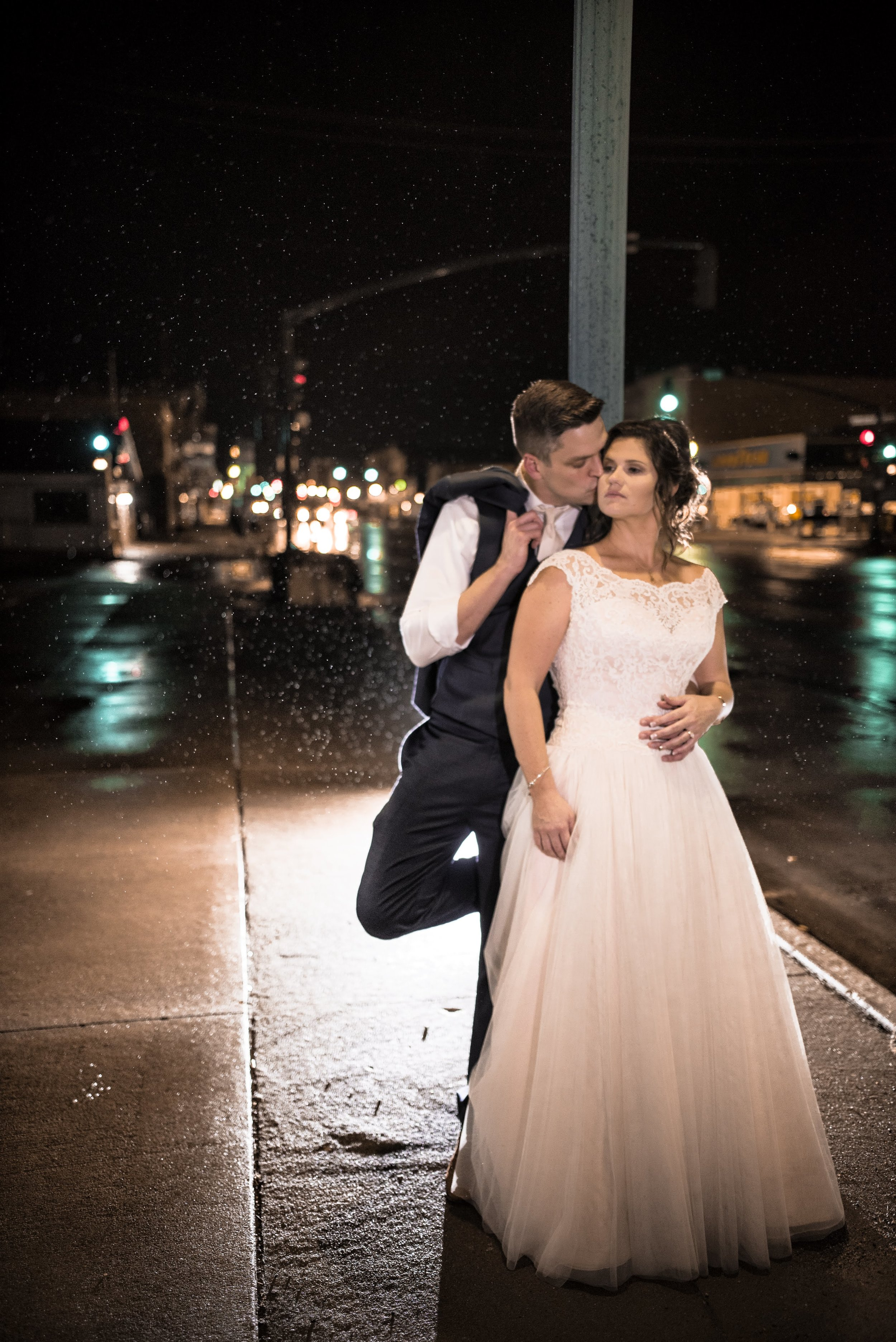 bride-groom-city-streets-kiss-cheek-in-rain.jpg