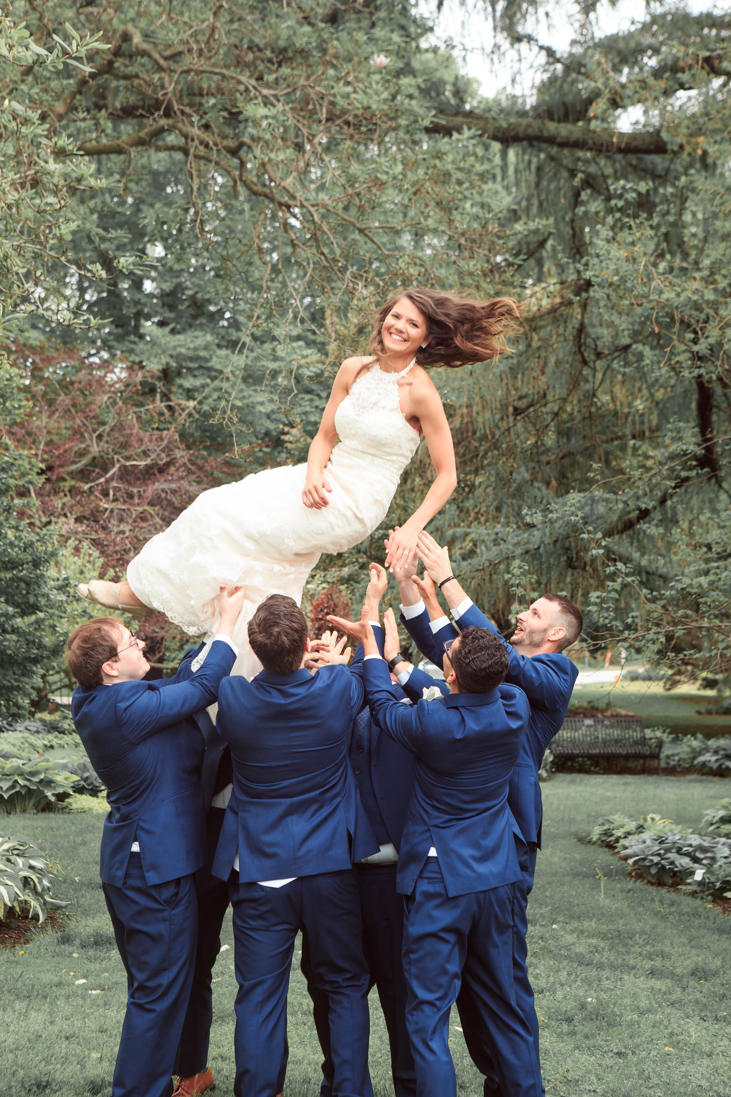 Throwing-bride-in-the-air-fun-wedding-pose-wih-groomsmen-with-bride.jpg