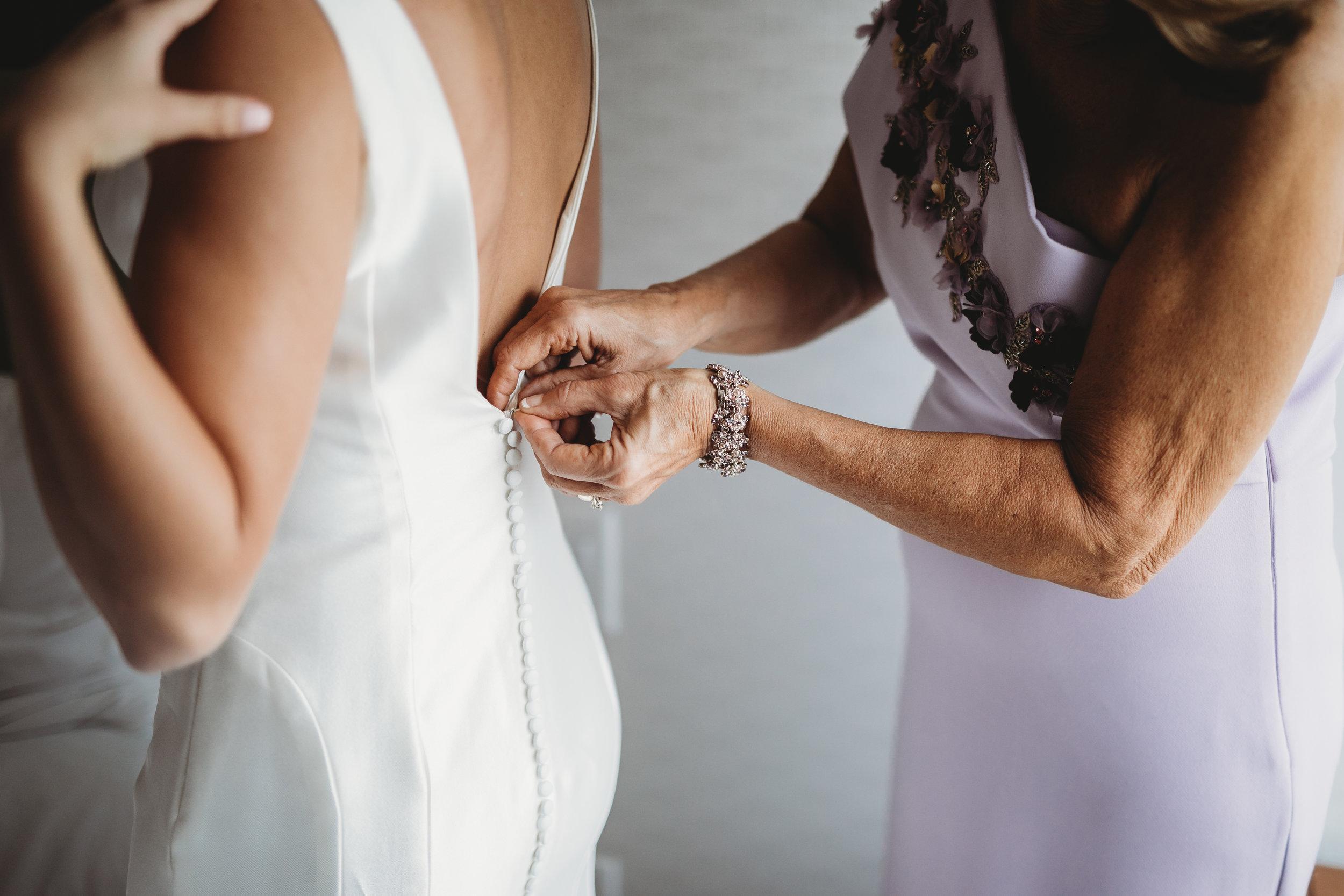 bride-getting-ready-in-hotel-lauren-ashley-studios-zipping-dress.jpg