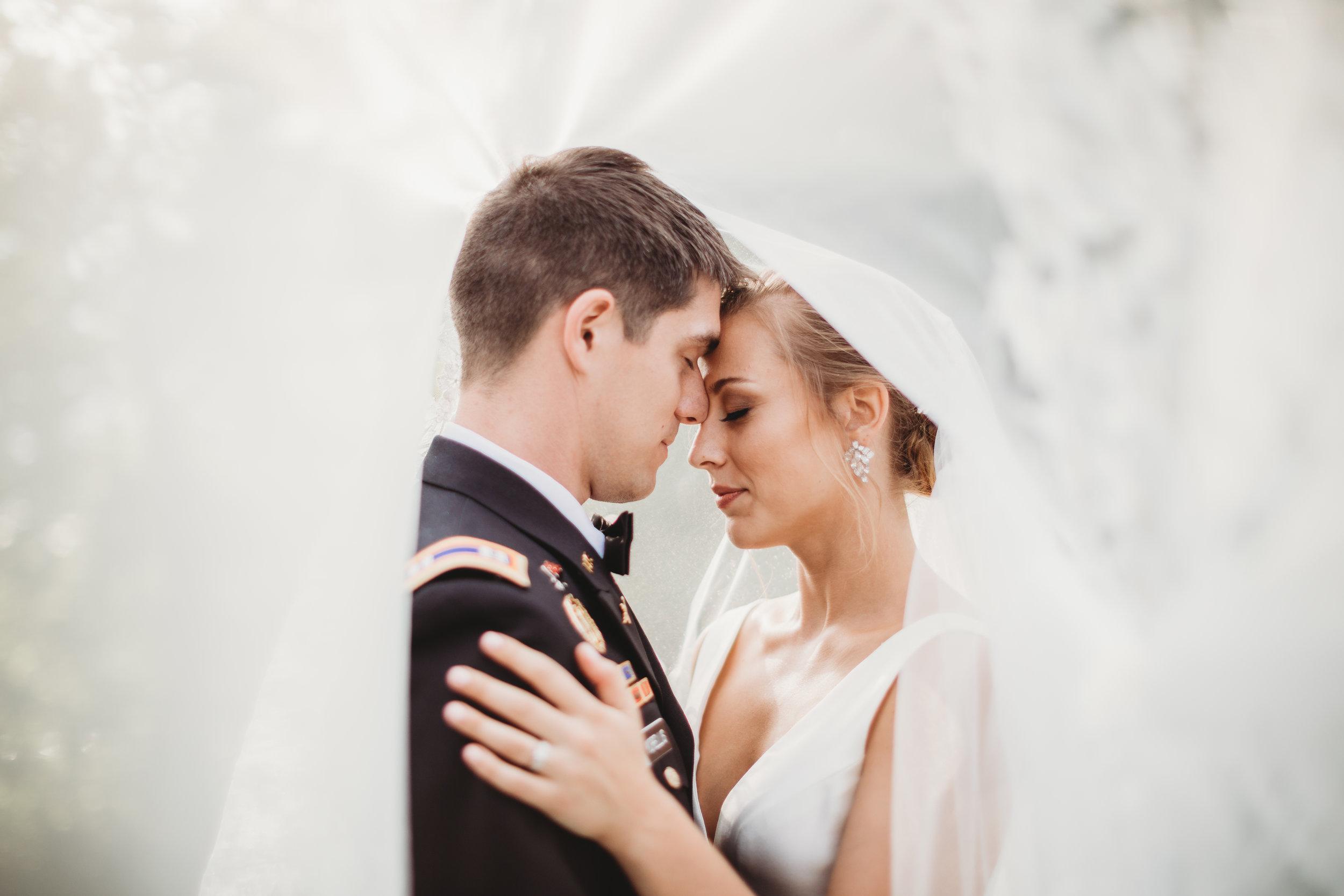 Bride-and-groom-wedding-pose-ideas-lauren-ashley-studios-under-veil.jpg