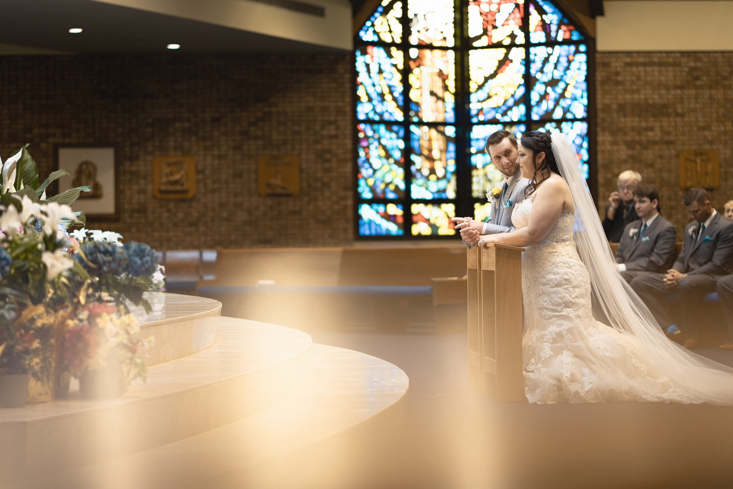 bride-groom-kneeling-on-alter-getting-married-in-catholic-church.jpg
