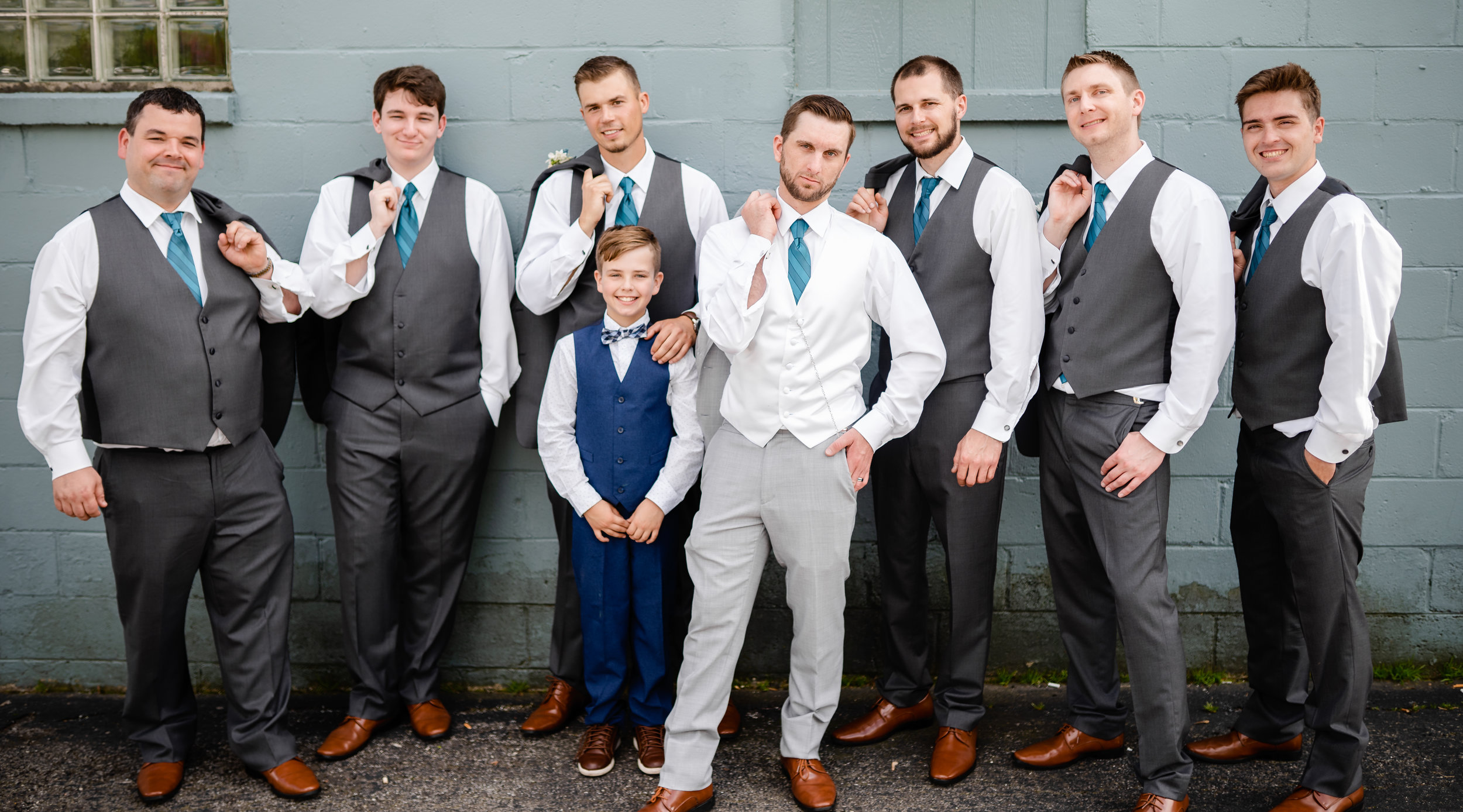 groom-and-groomsmen-power-pose-turquoise-ties-grey-vests-cinder-block-wall.jpg