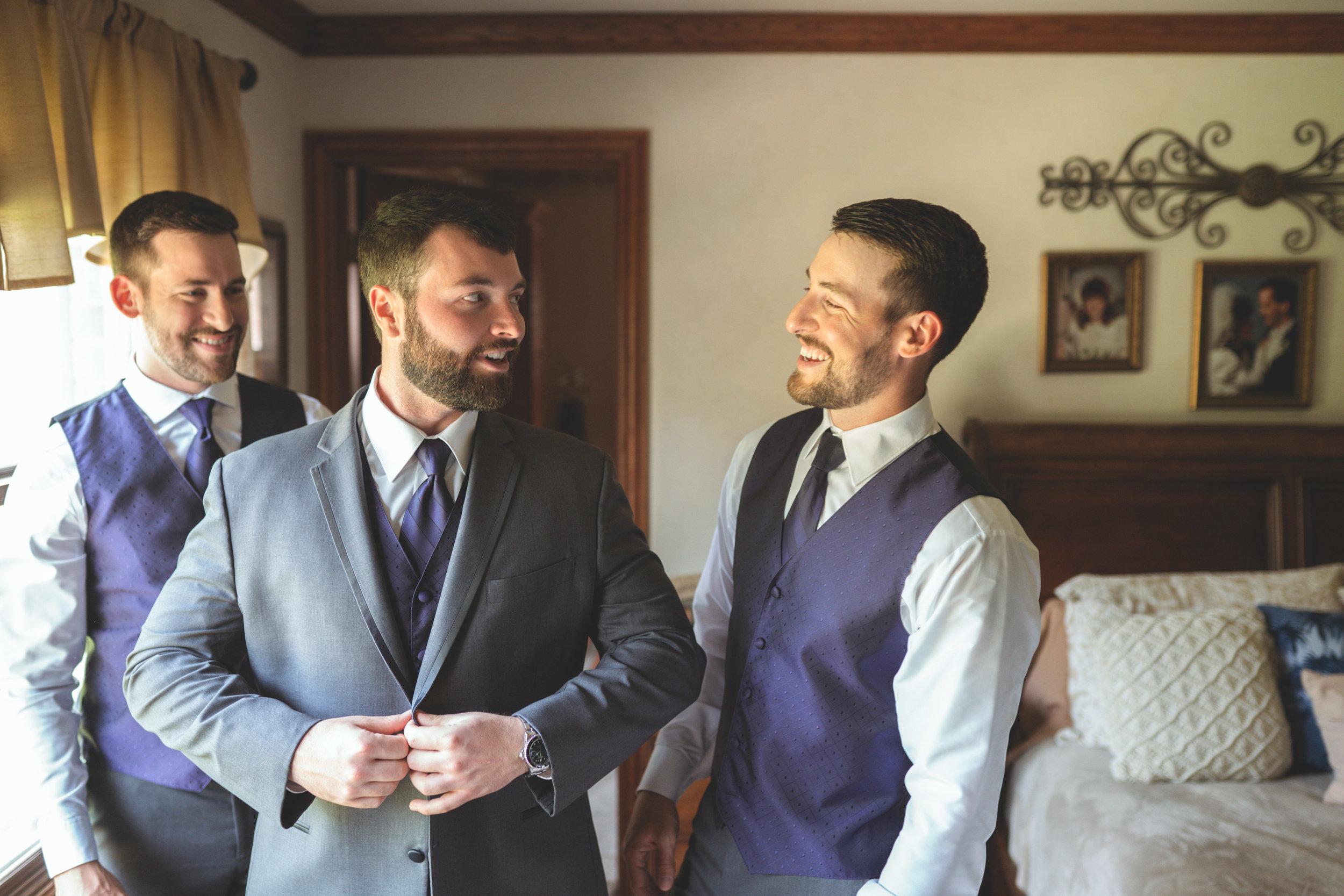 groom-best-man-groomsman-getting-ready-putting-on-jacket.jpg