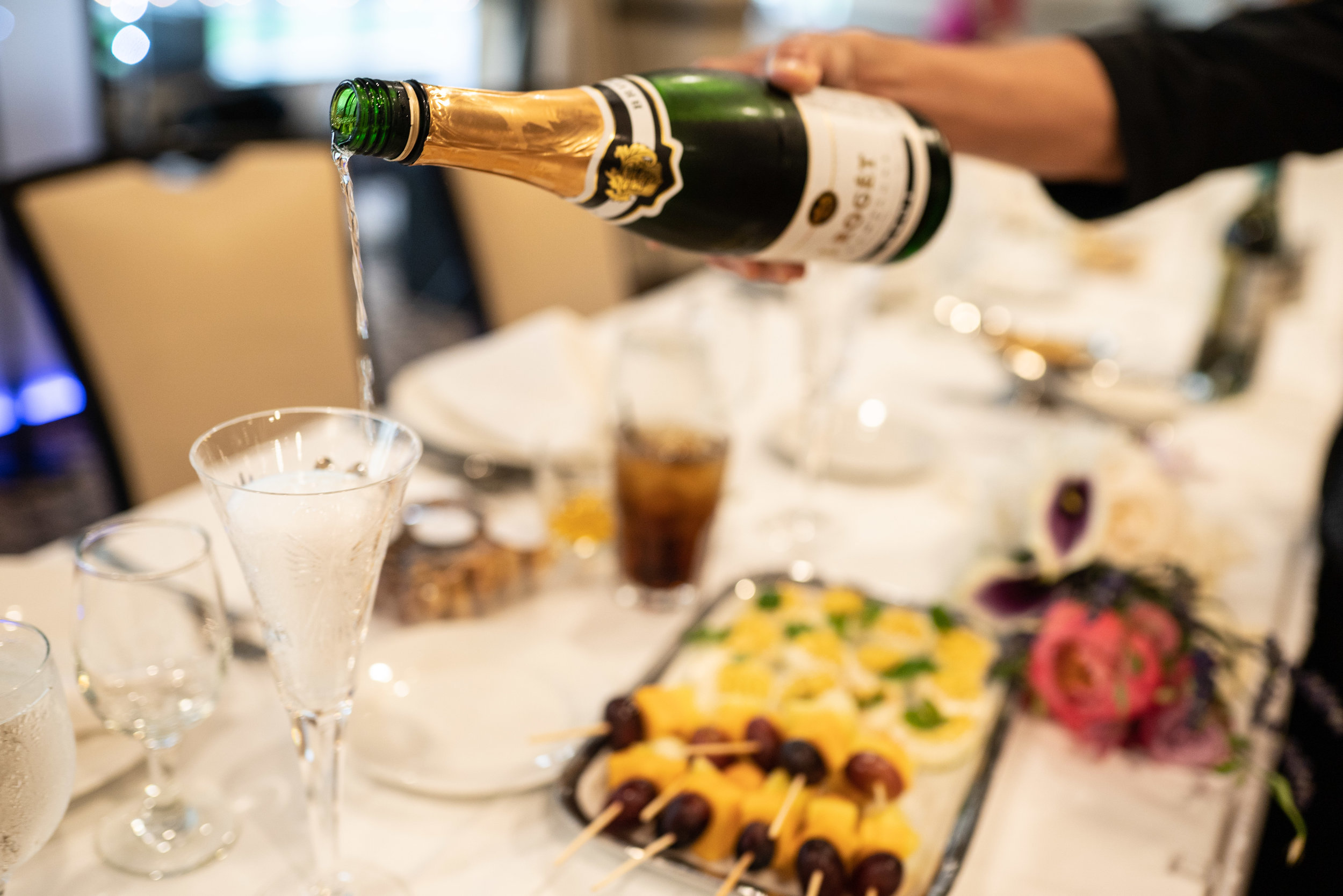wedding-detail-hors-d'oeuvres-champagne-pour-at-head-table-for-bride-and-groom.jpg