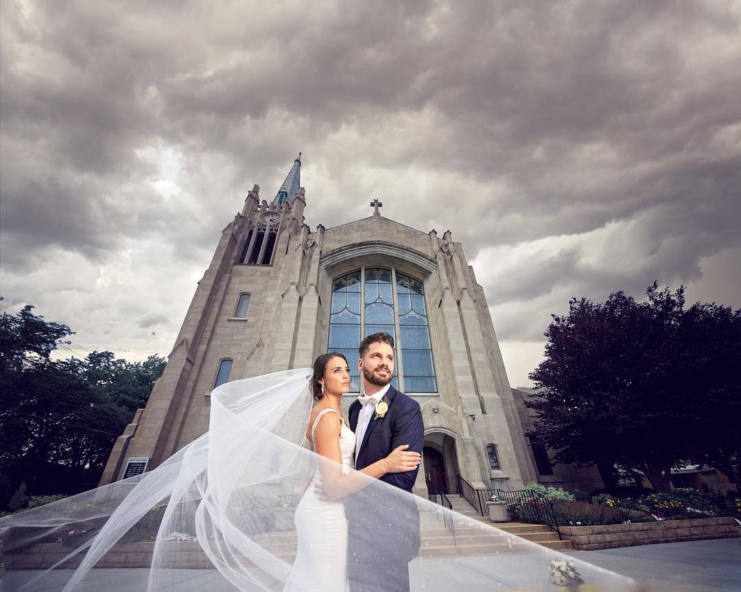 bride-and-groom-with-flowing-veil-in-front-of-cathedral-church.jpg