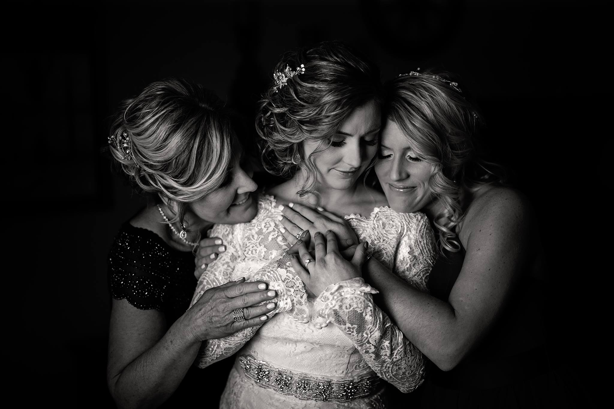 black-and-white-bride-mother-and-sister-hug-and-love-before-wedding.jpg