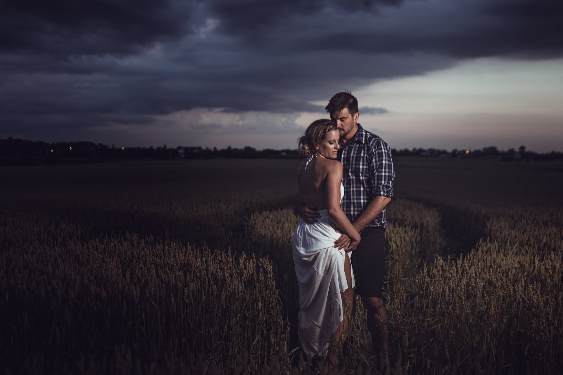 enagement-photography-couple-embracing-in-field-with-storm-approaching.jpg