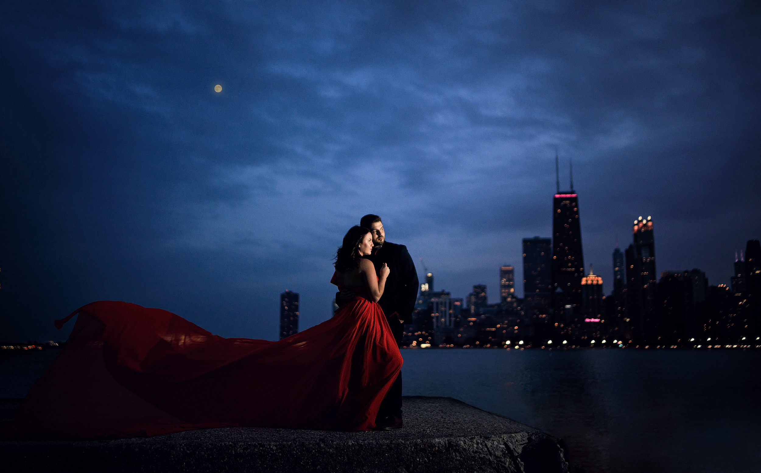 north-beach-downtown-chicago-engagement-session-flowing-red-dress-with-moon-over-john-hancock-building.jpg